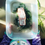 A plastic container being held by a child's hands with a piece of salmon covered in salt, and on a bed of fresh dill inside.