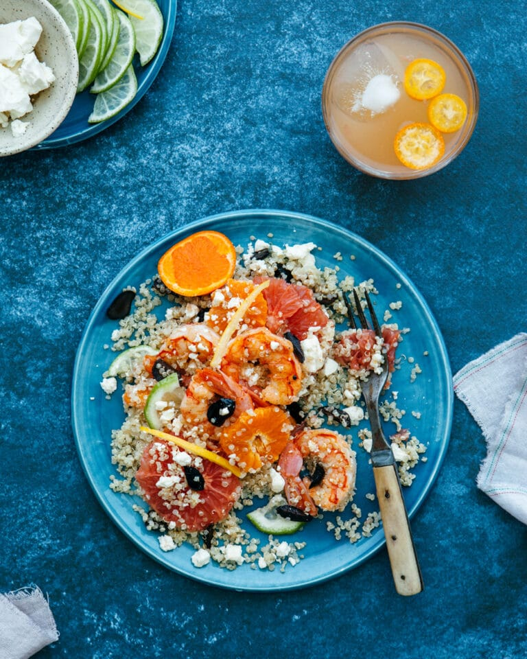 A single serving of quinoa citrus salad with shrimp on a blue plate with a blue background.