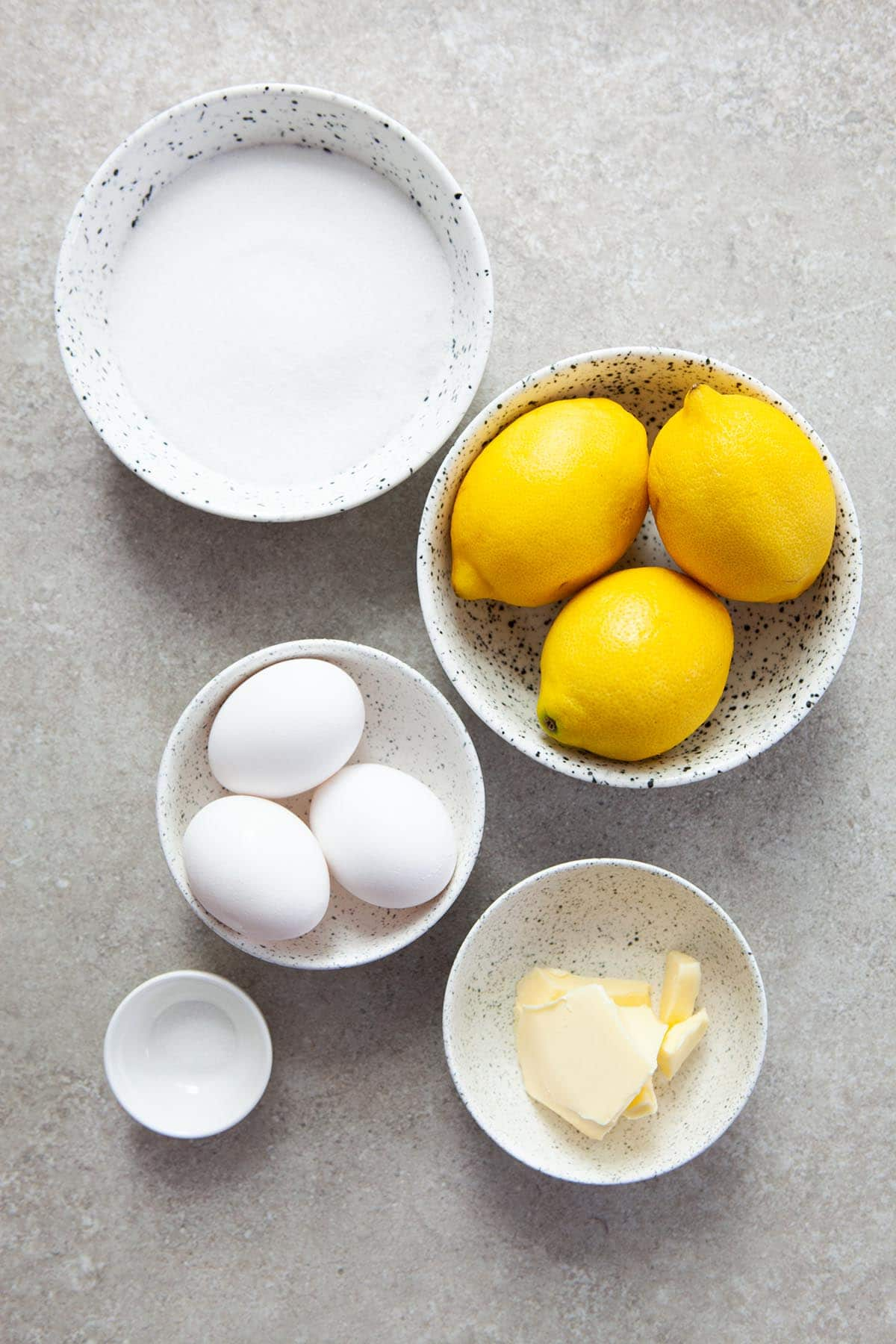 Ingredients to make lemon curd laid out in small bowls on a stone surface.