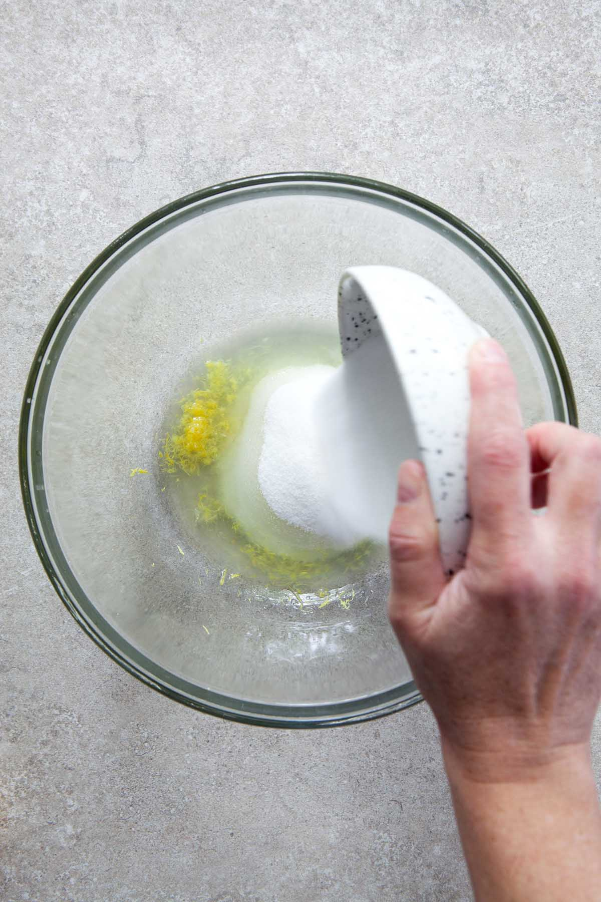 A hand pouring sugar from a small speckled bowl into a large glass bowl with lemon zest and juice.