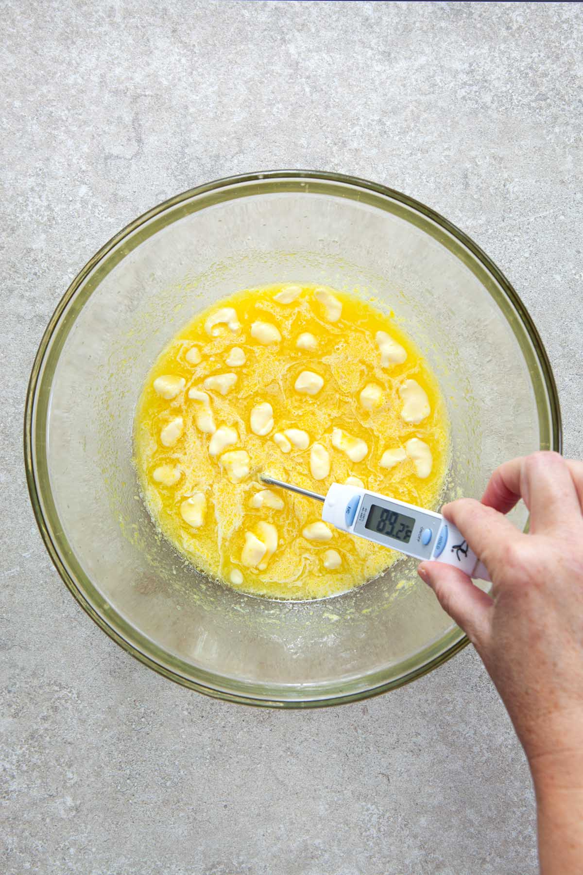 A hand taking a temperature reading with a thermometer in a glass bowl of eggs, lemon juice, and butter.