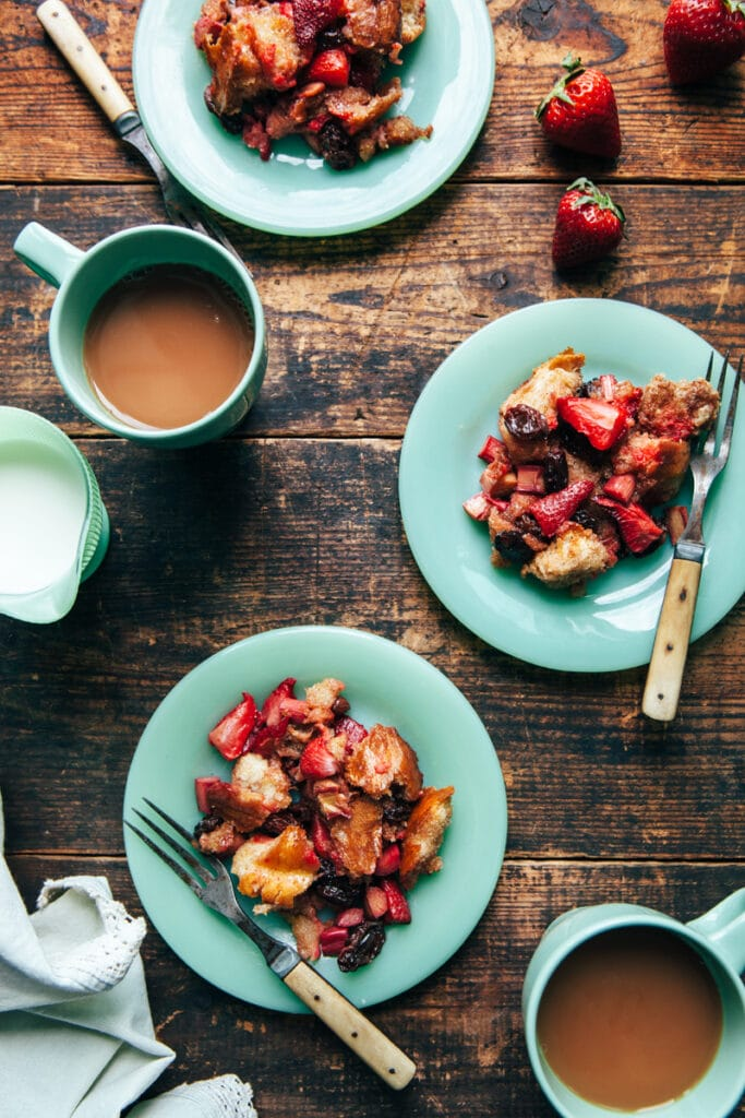 Three servings of strawberry rhubarb bread pudding on green plates with two cups of tea on a harvest table.