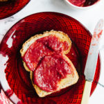 A slice of toast smeared with maple rhubarb jam on a red glass plate.