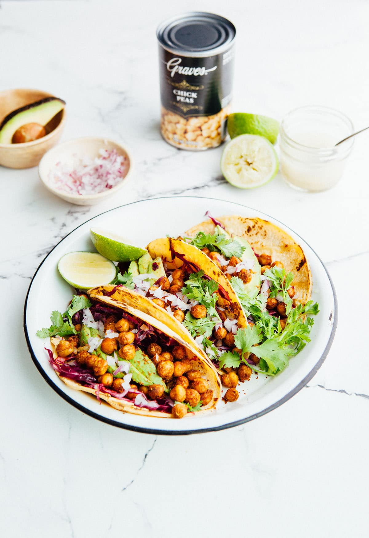Three roasted chickpea tacos standing upright in a white round enamel plate with a can of Graves chickpeas in the background.