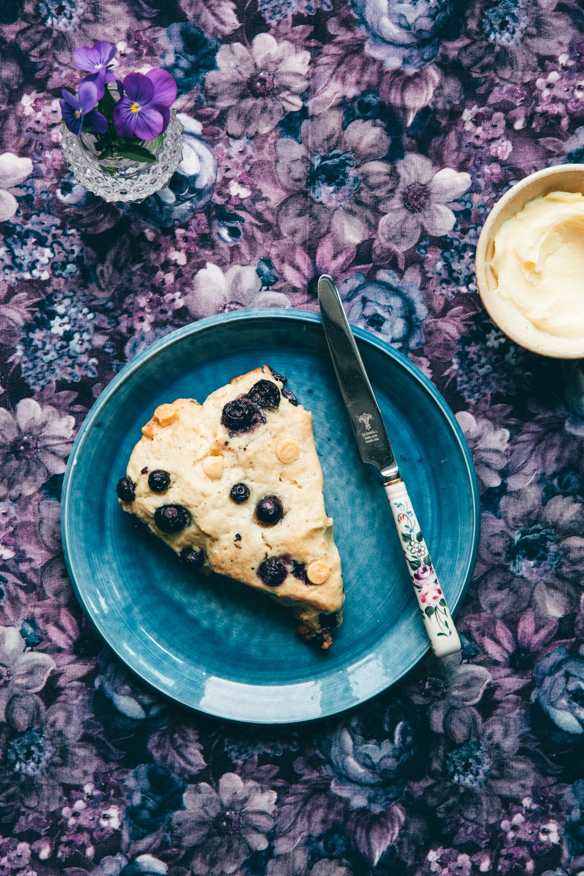 A blueberry white chocolate scone on a blue plate on a flowered tablecloth.