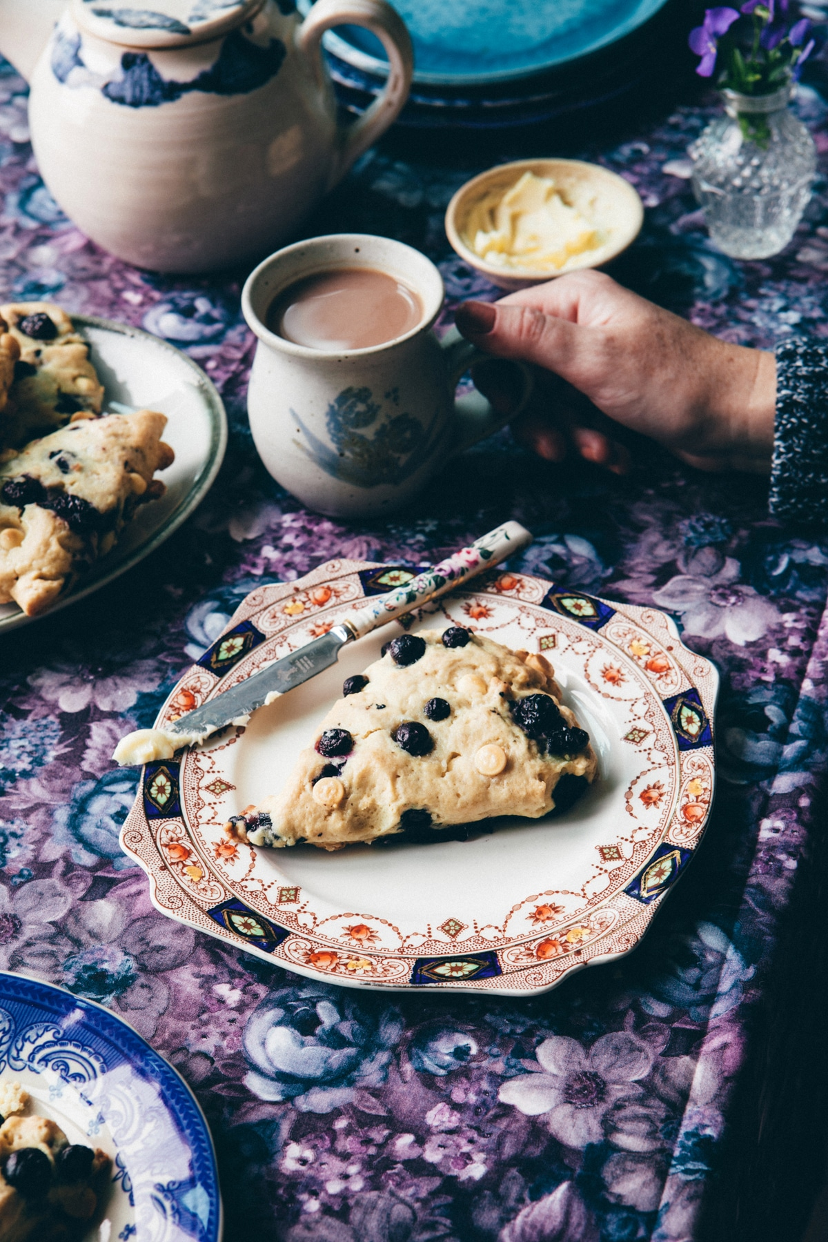 A table filled with plates of blueberry white chocolate scones and a woman's hand holding a cup of tea.