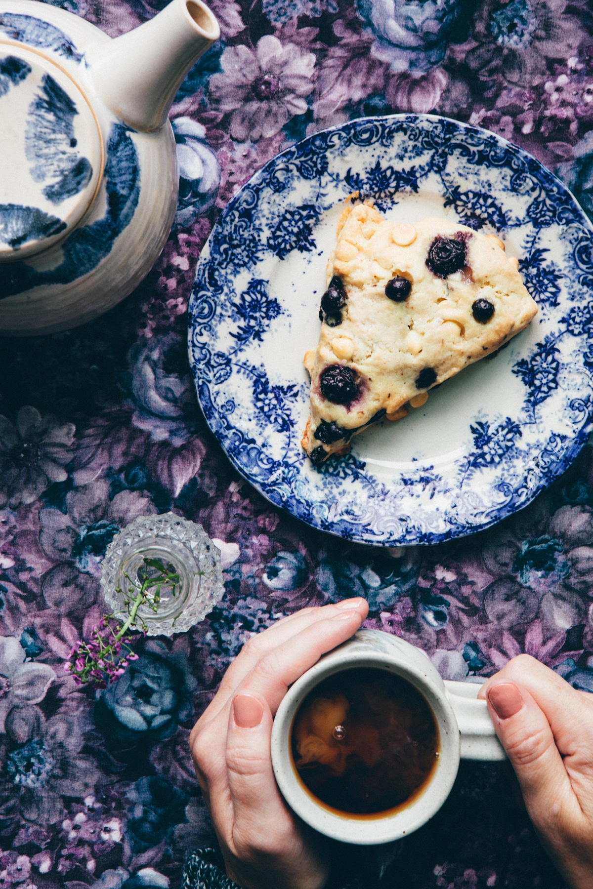Hands holding a mug of tea next to a plate with a blueberry white chocolate scones.