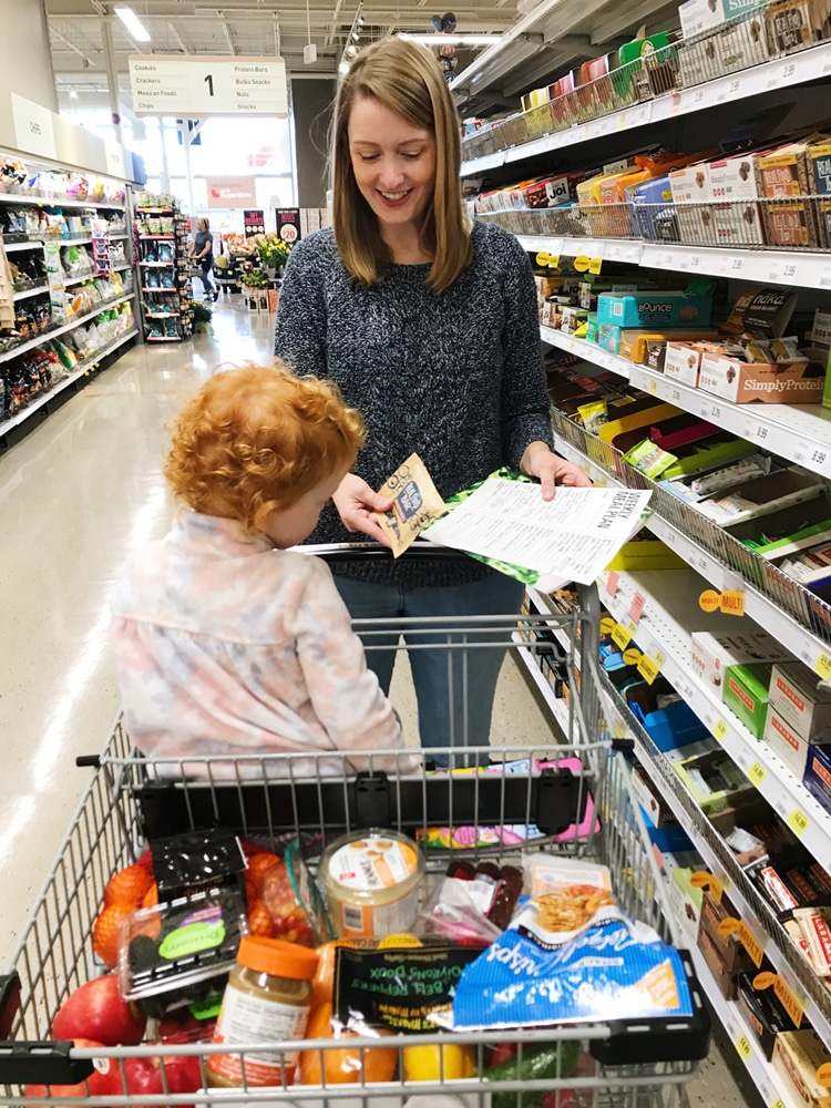 A woman shoping with a child in the seat of the shopping cart.