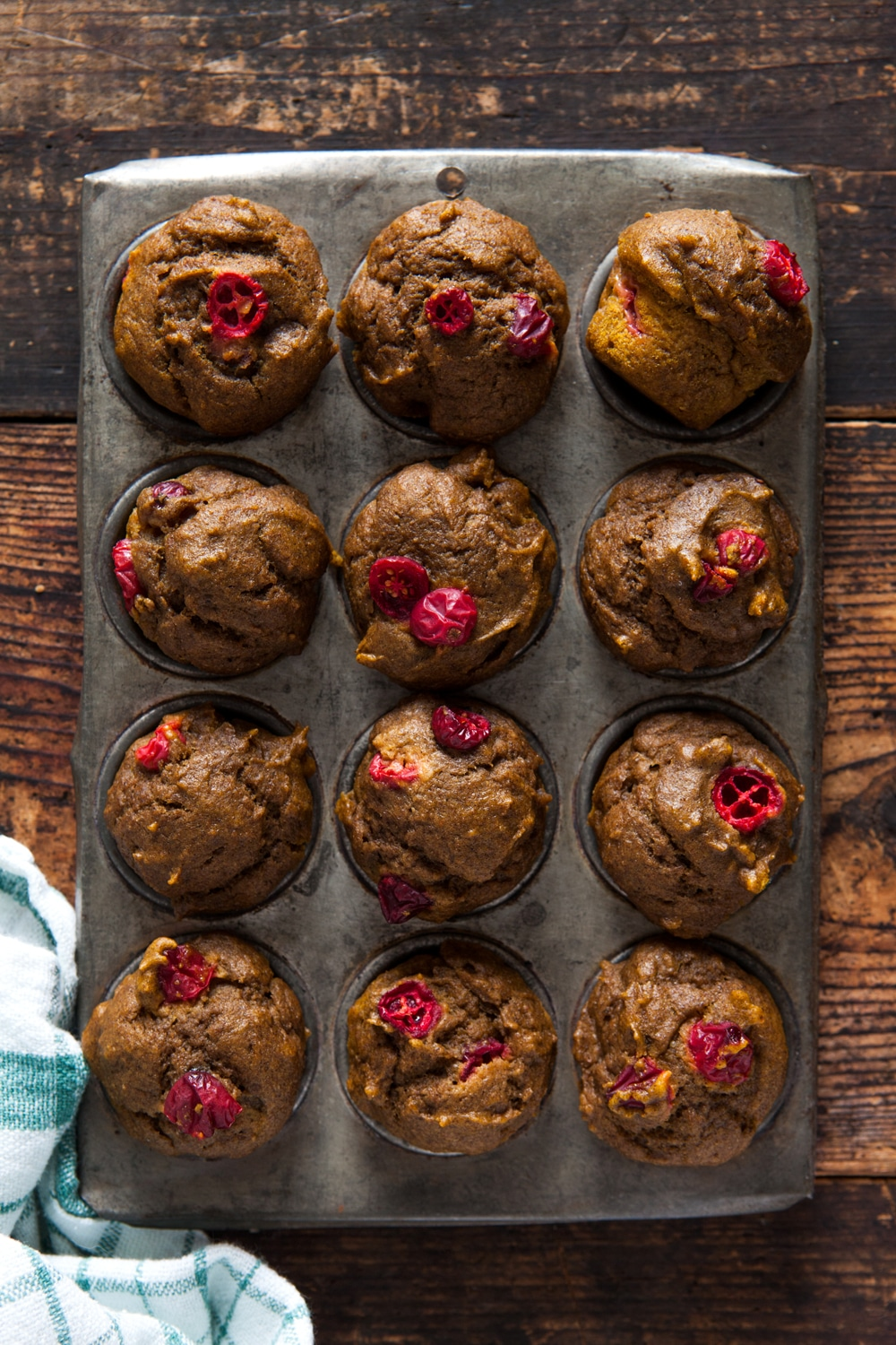 Overhead of mini pumpkin cranberry muffins in a baking tin.