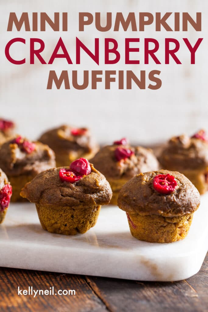 Mini pumpkin cranberry muffins on a marble board.