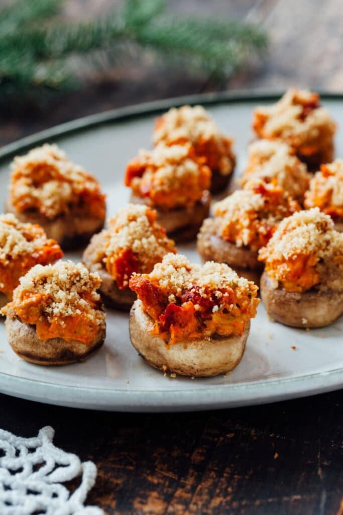 Close up photo of vegan sun dried tomato & olive stuffed mushrooms.