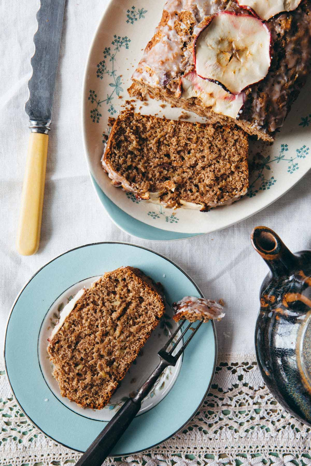 An apple loaf on a platter with a slice on a plate with a fork.