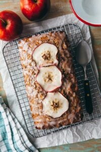 An apple loaf cake on a wire rack topped with apple cider glaze.