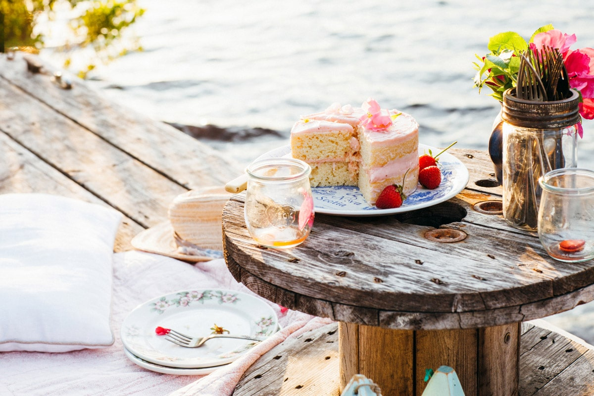 Lemon buttermilk cake with strawberry jam-cream cheese icing on a small table on a dock.