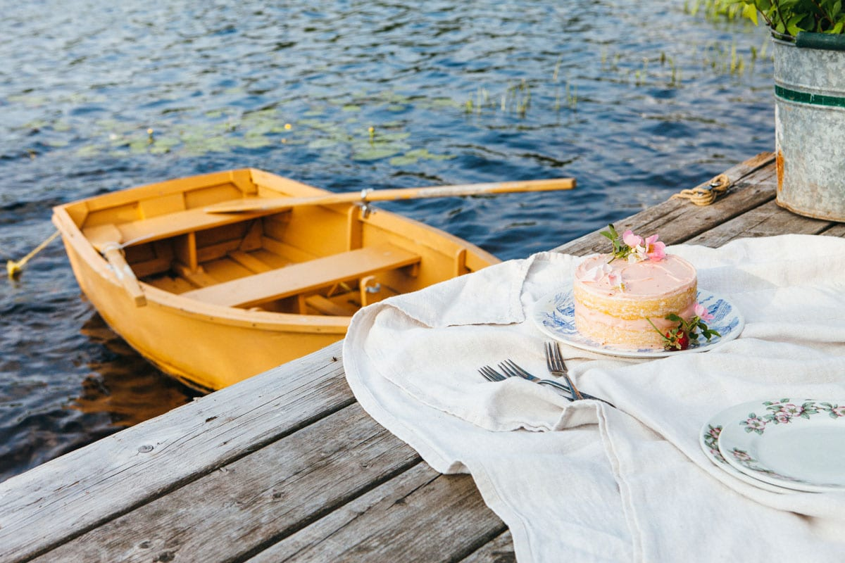 A lemon buttermilk cake on a plate on a dock next to a yellow rowboat.