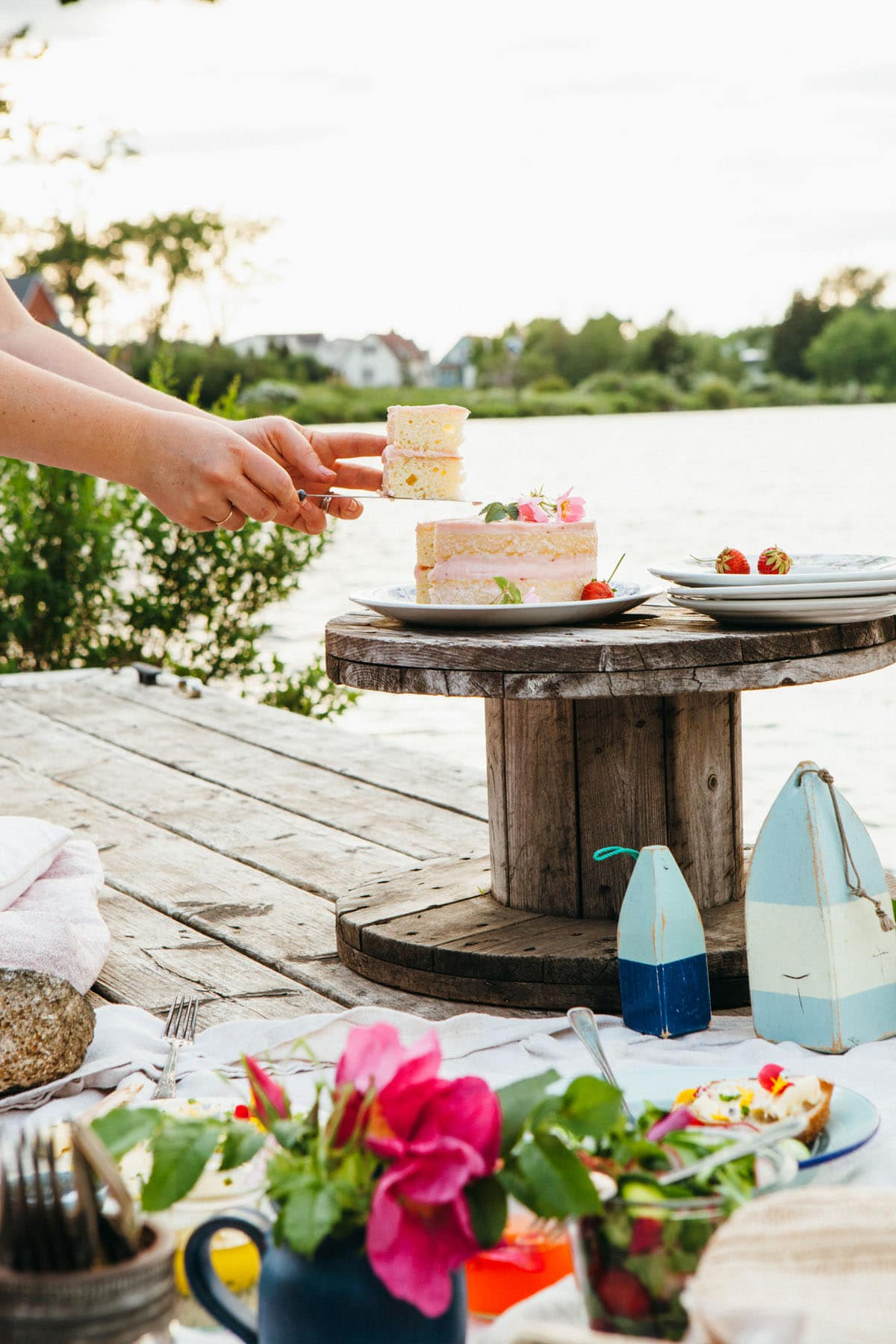 A woman's hands holding a piece of cake up after slicing it from a whole cake on a small table on a dock.