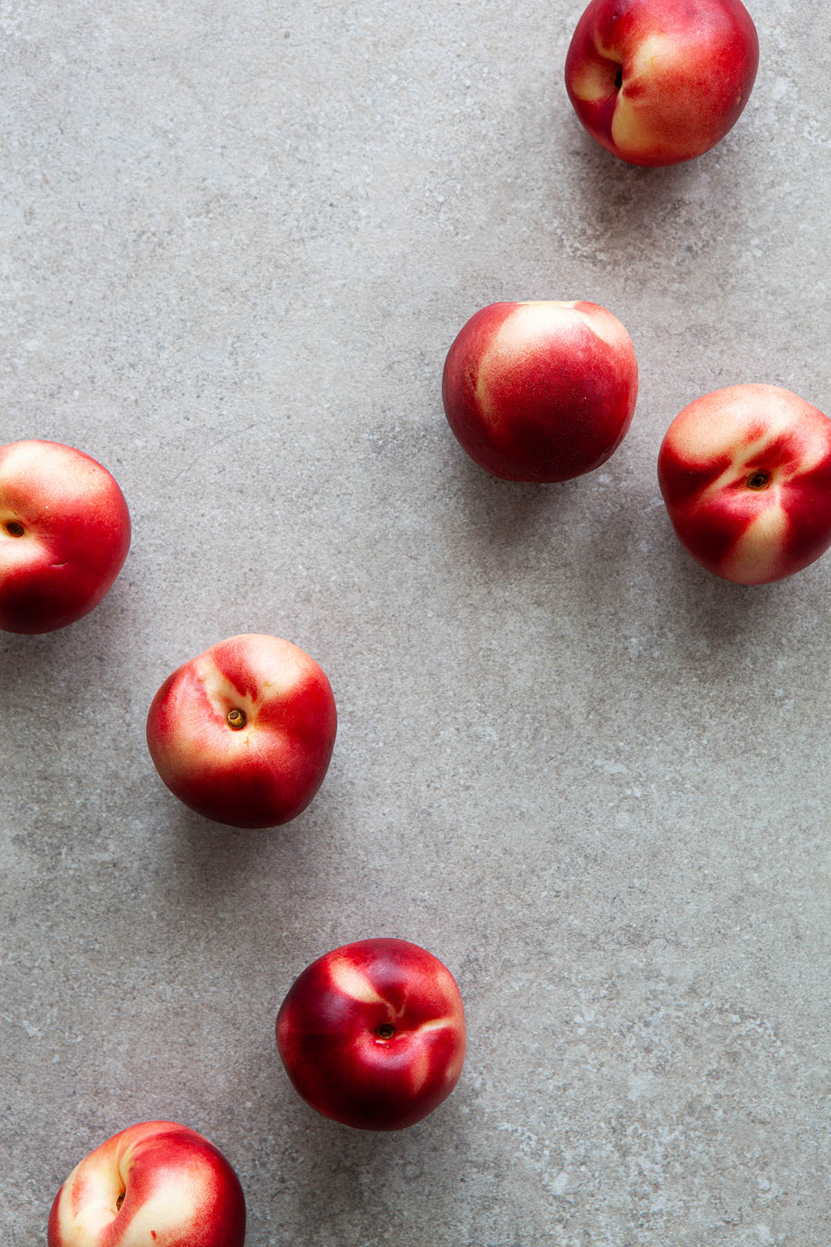 Seven nectarines on a stone background.