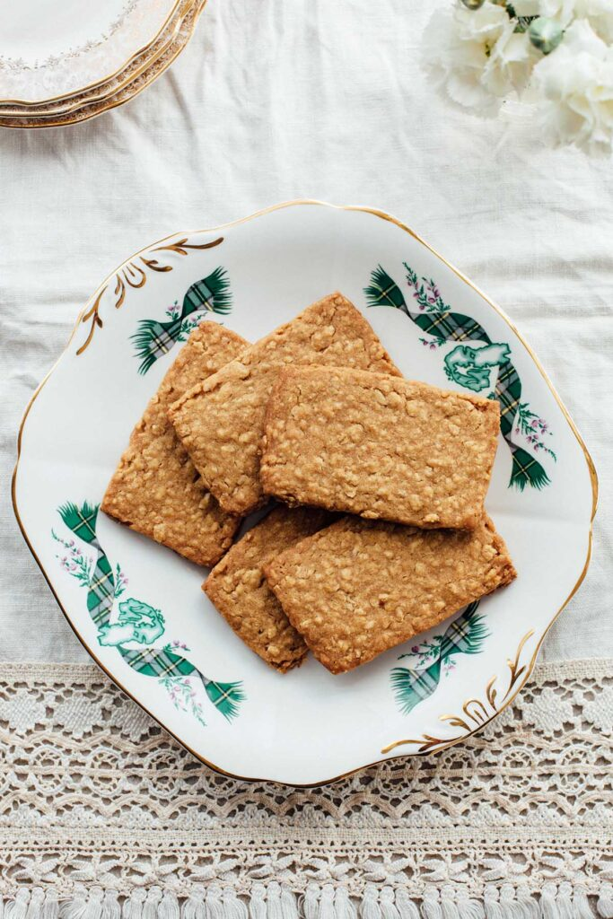 A platter of Nova Scotia oatcakes on a table with plates and a vase of white flowers.