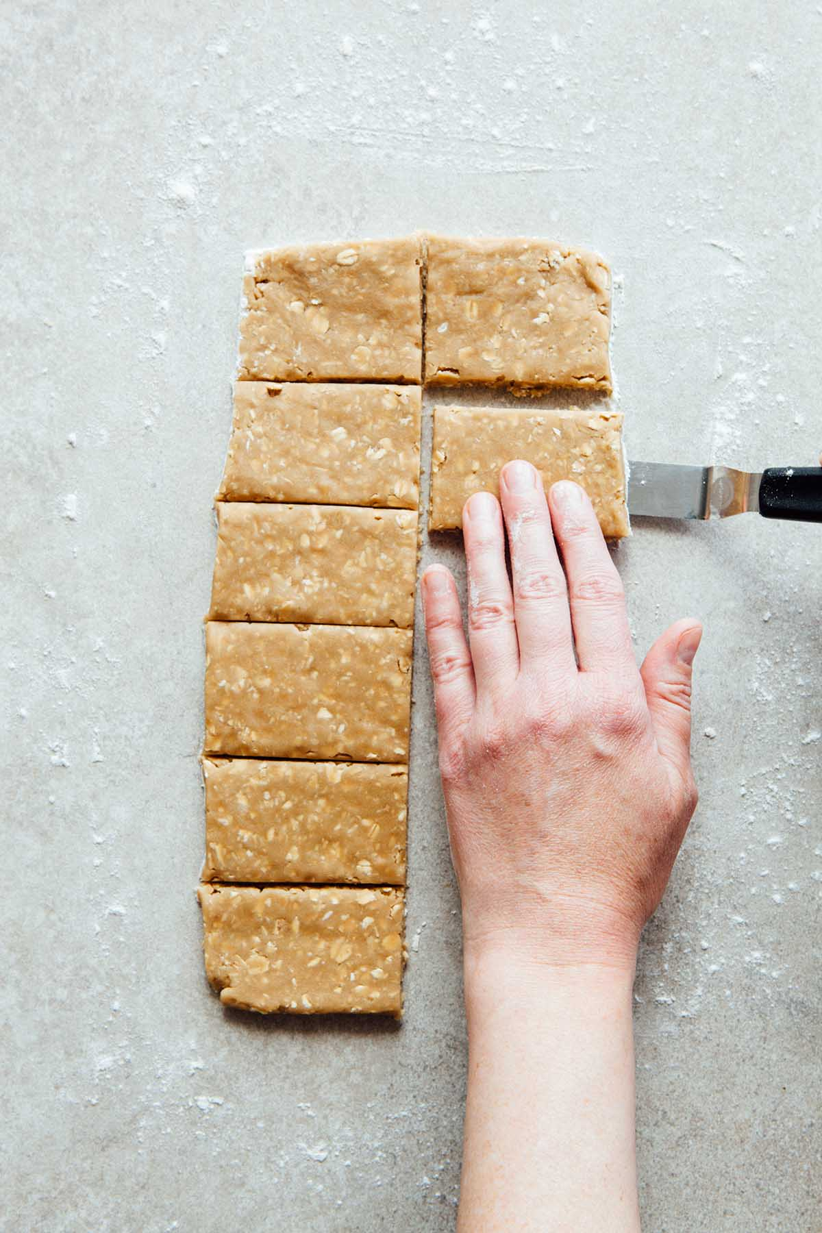 A hand lifting an oatcake with an offset spatula.