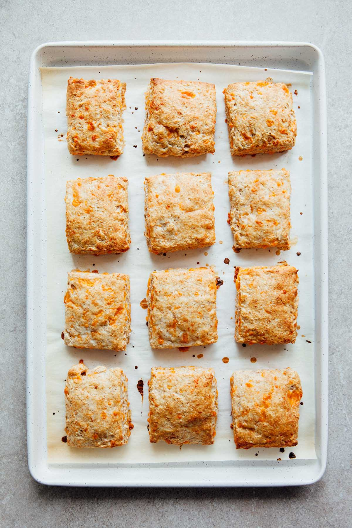 Overhead photo of a full pan of a dozen baked whole wheat cheese biscuits.