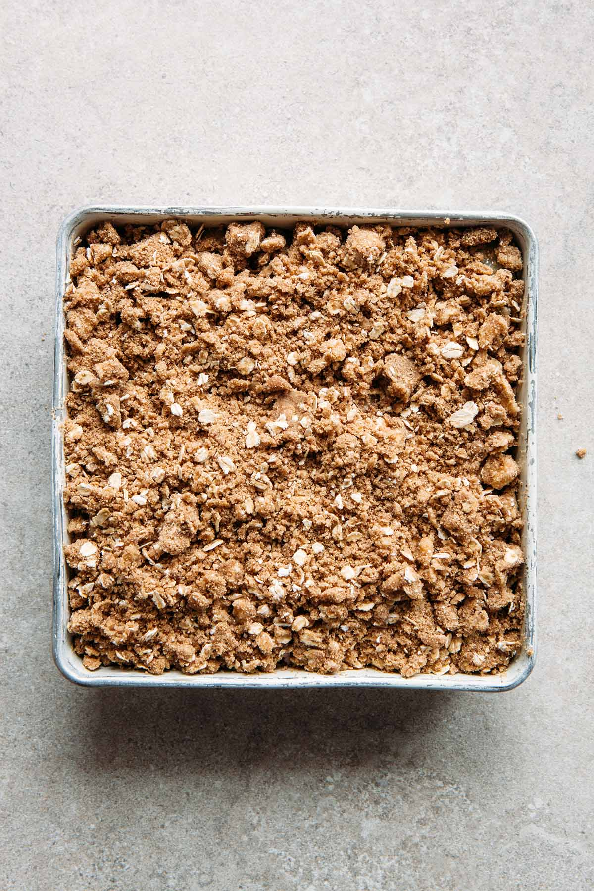 Unbaked gluten-free rhubarb crisp in a square pan.