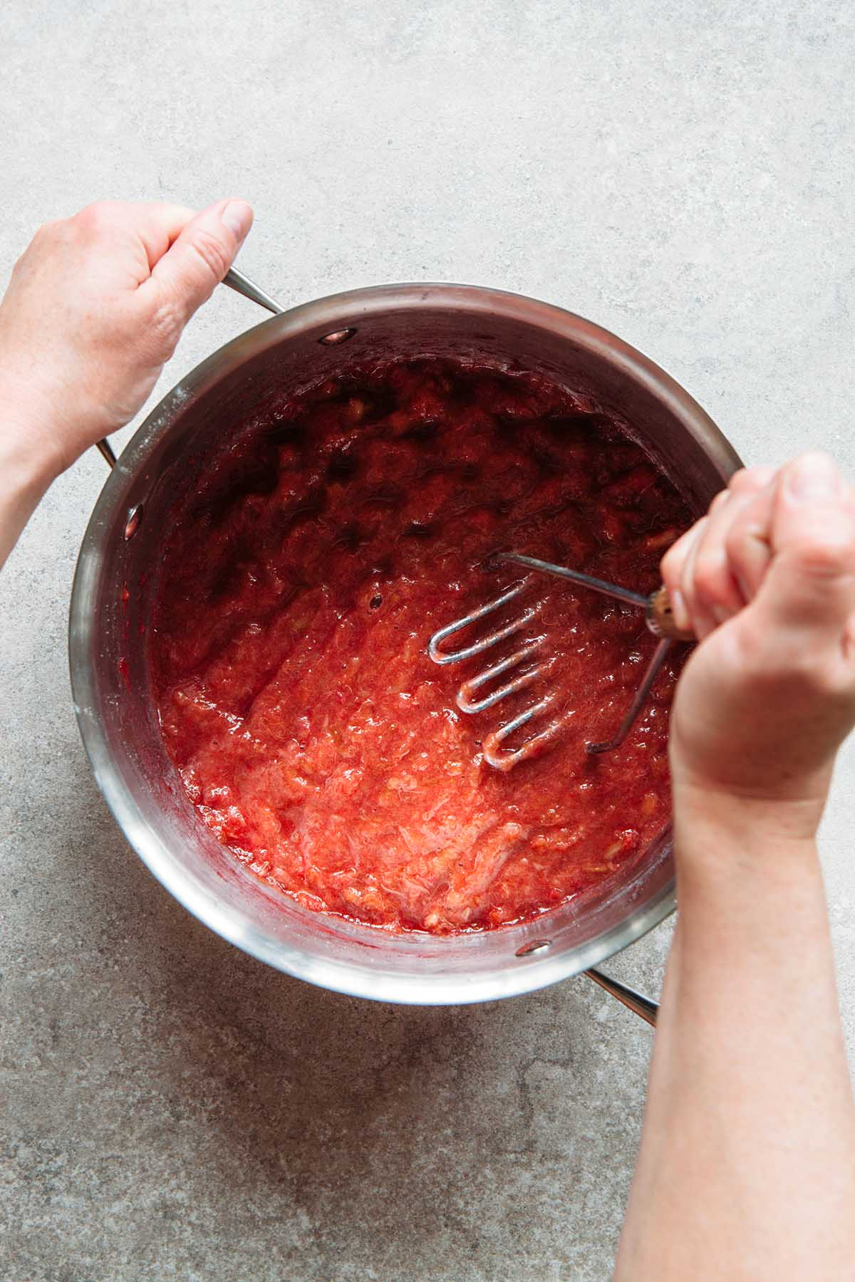A hand crushing cooked rhubarb with a potato masher.
