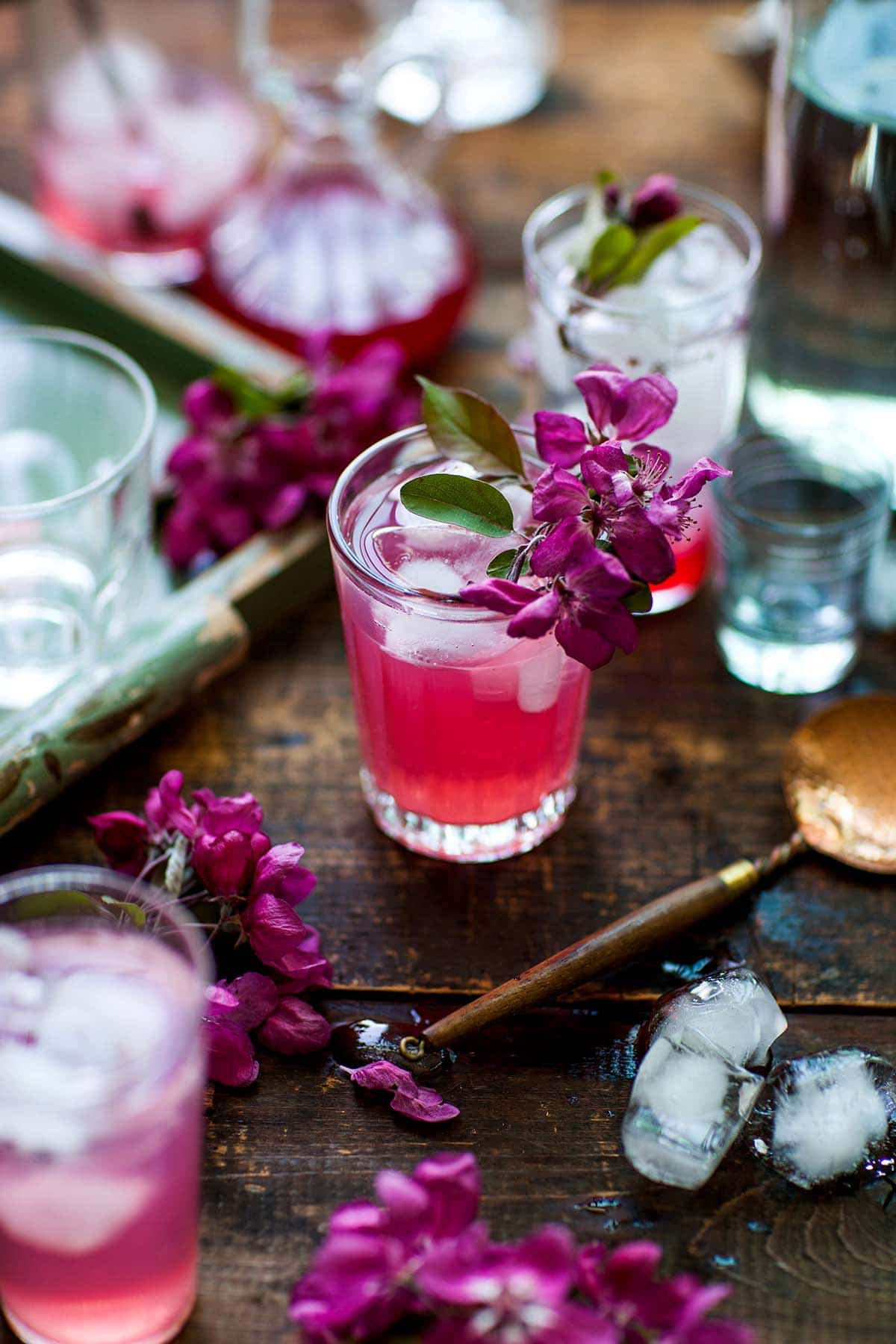 One bright pink cocktail made with rhubarb simple syrup in a small glass, garnished with pink apple blossoms.