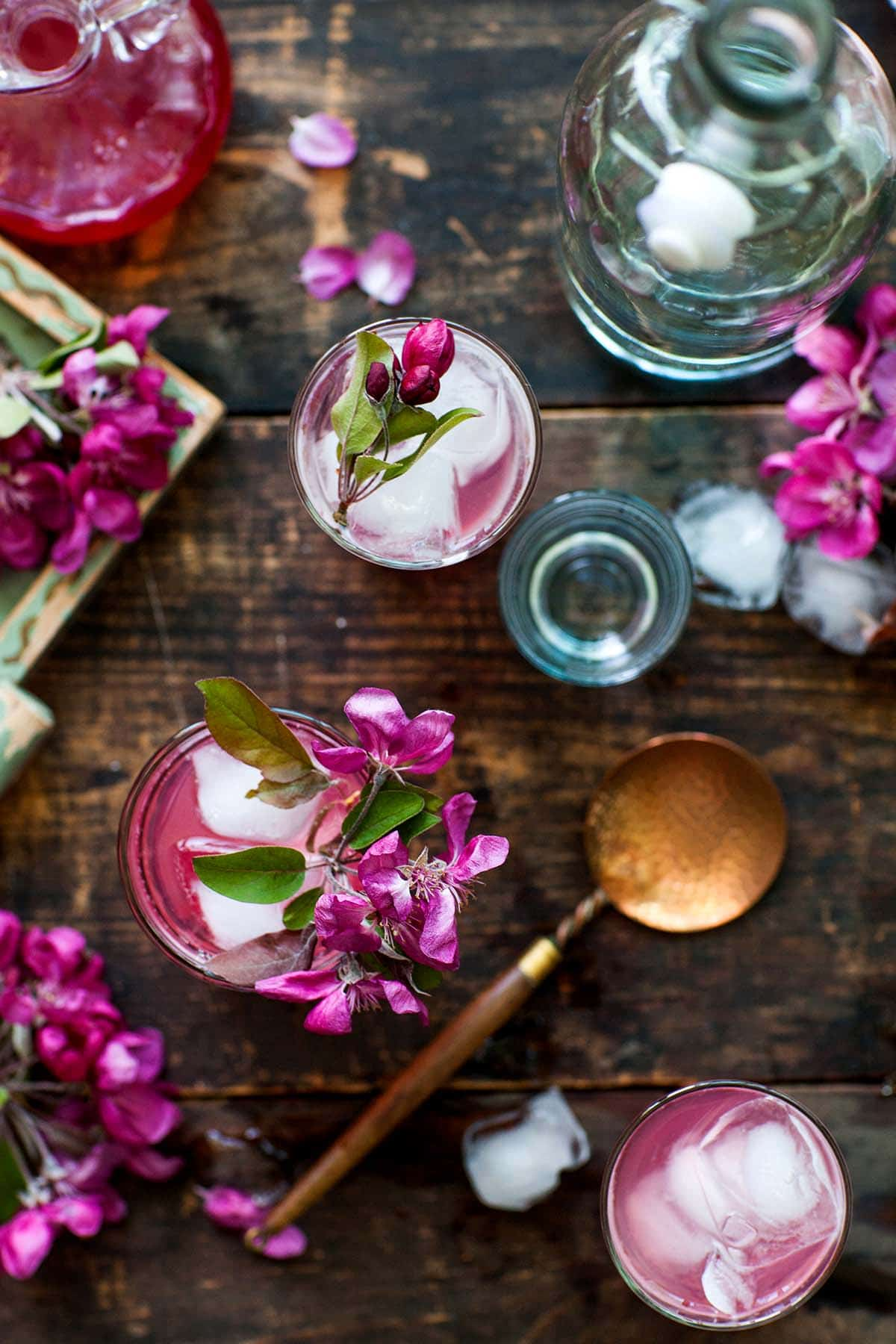 Overhead shot of cocktails with ice and barware garnished with pink flowers.