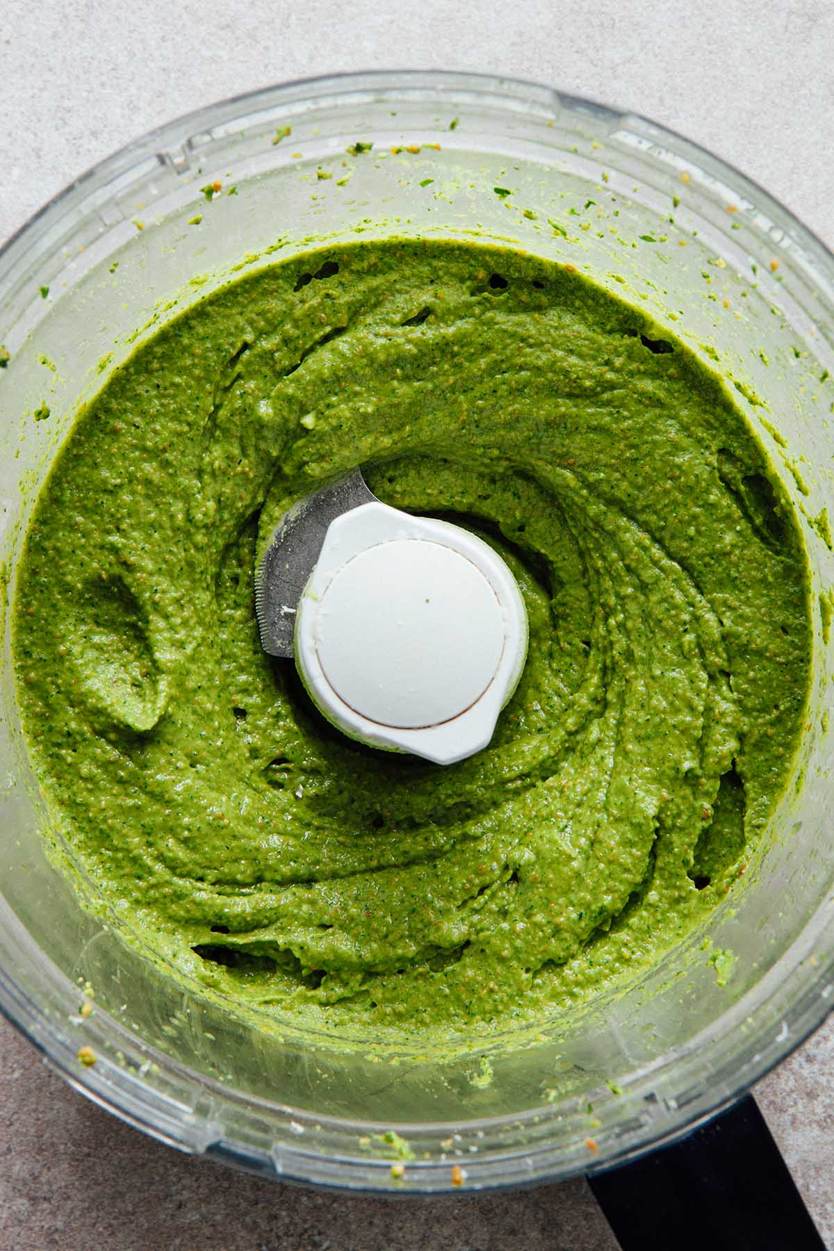 Pesto in the bowl of a food processor after the olive oil has been slowly dribbled in.