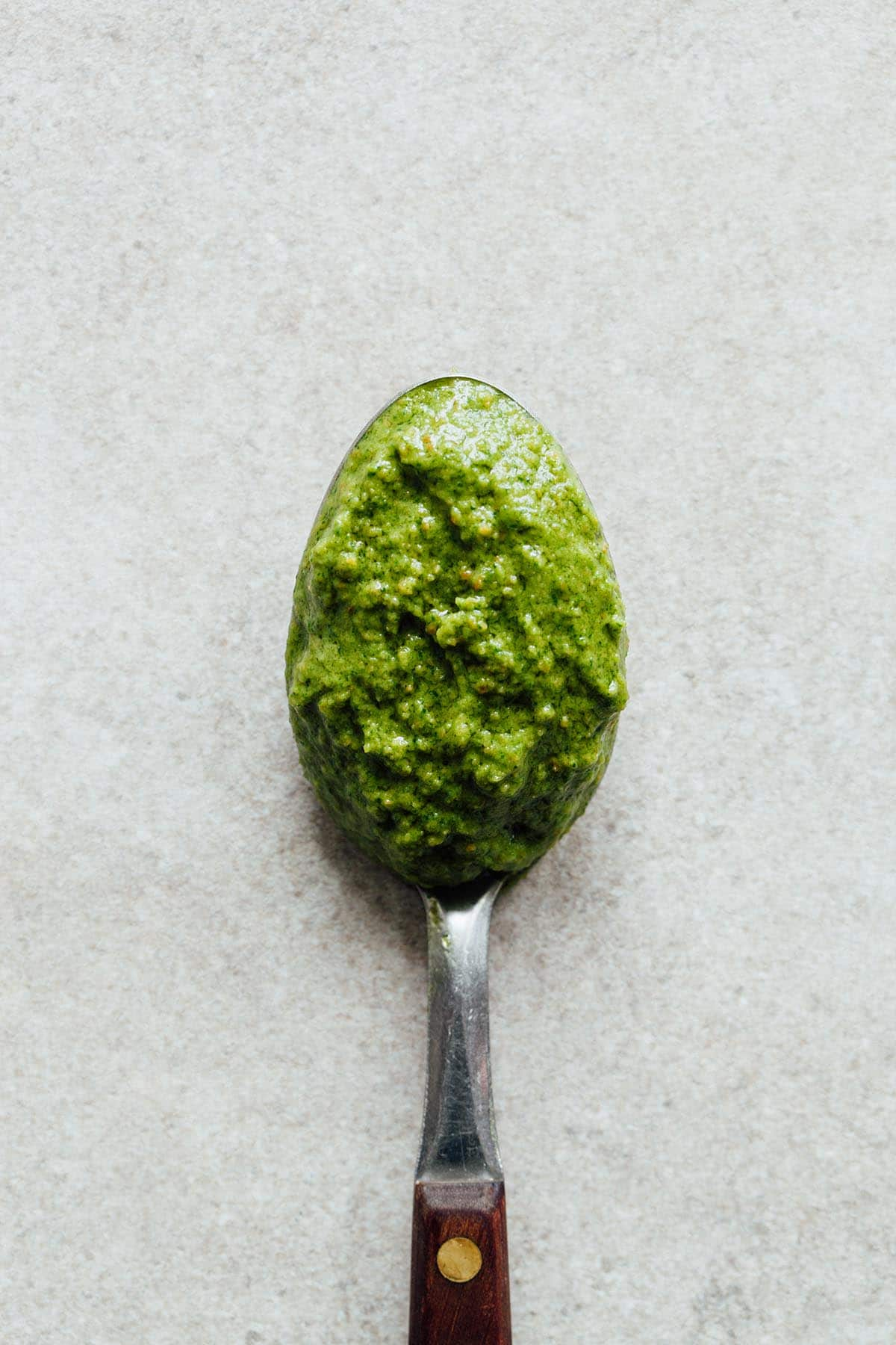 A spoonful of spinach arugula pesto laying on a stone surface.