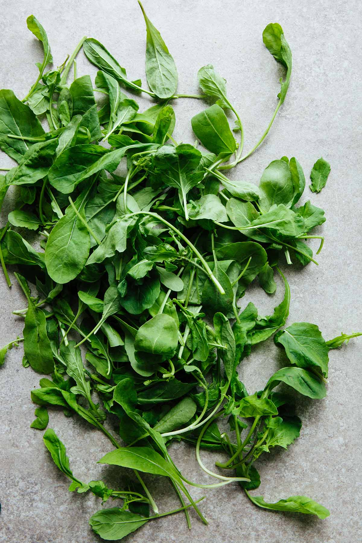 A pile of fresh arugula leaves on a stone surface.