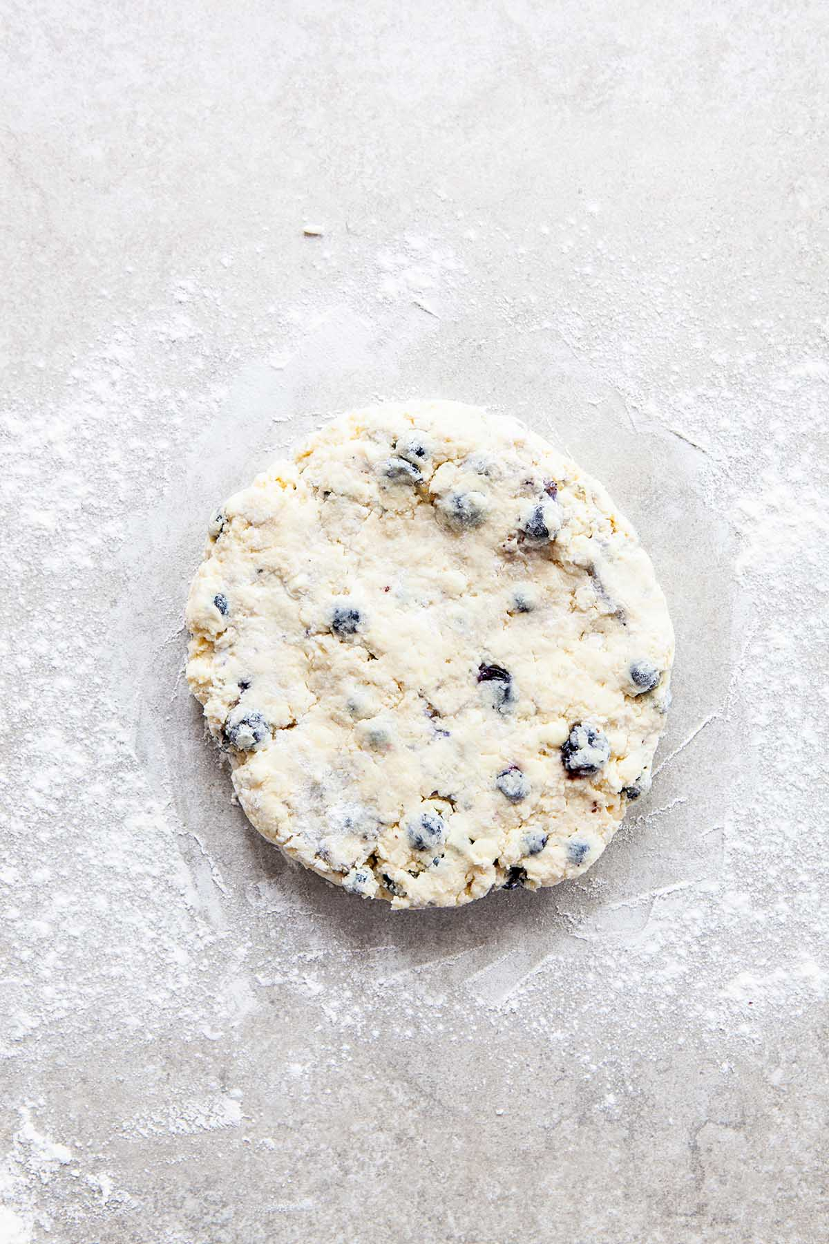 A round disc of unbaked scone dough on a floured stone surface.