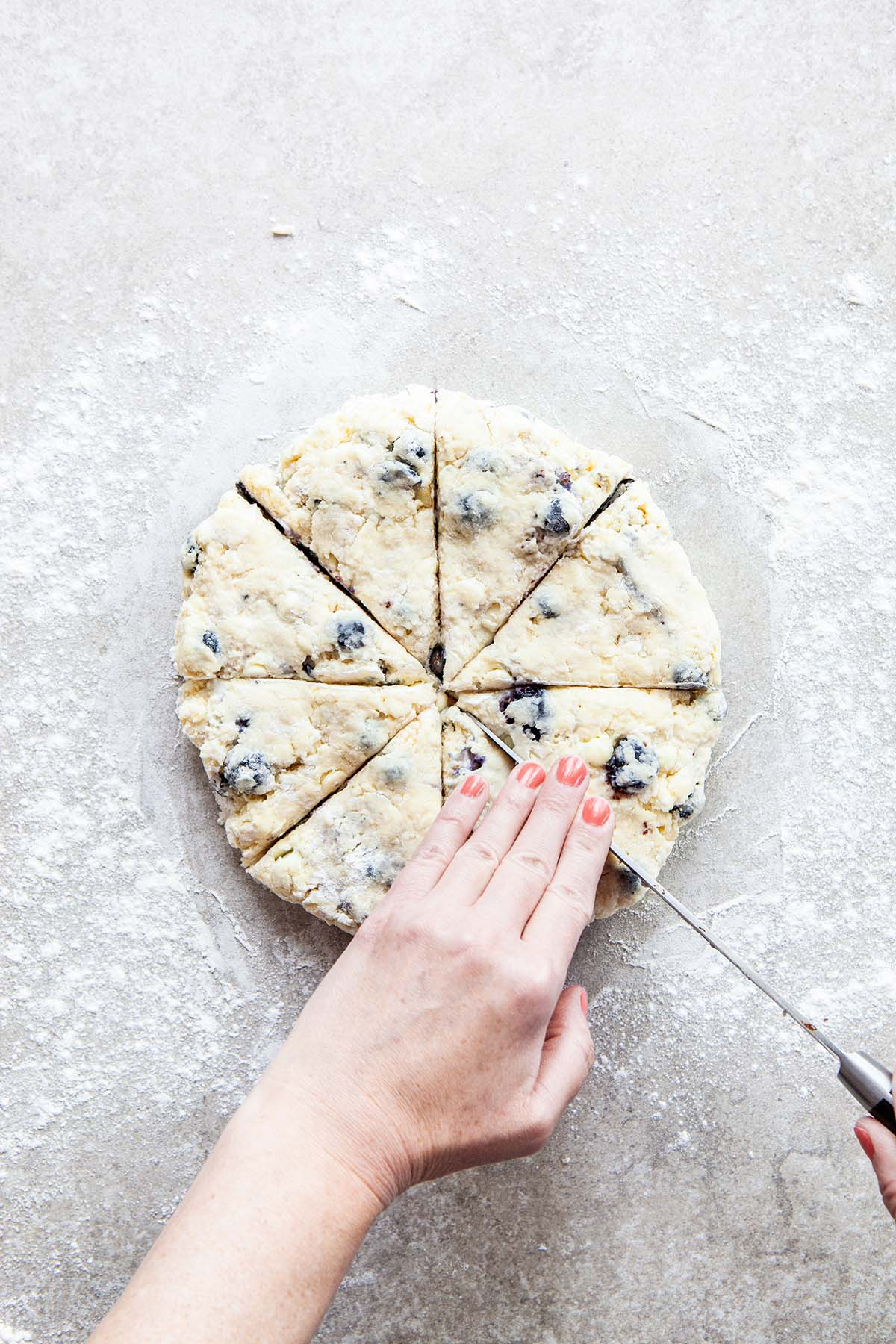 Hands cutting a disc of scone dough into wedges with a long knife on a floured stone surface.