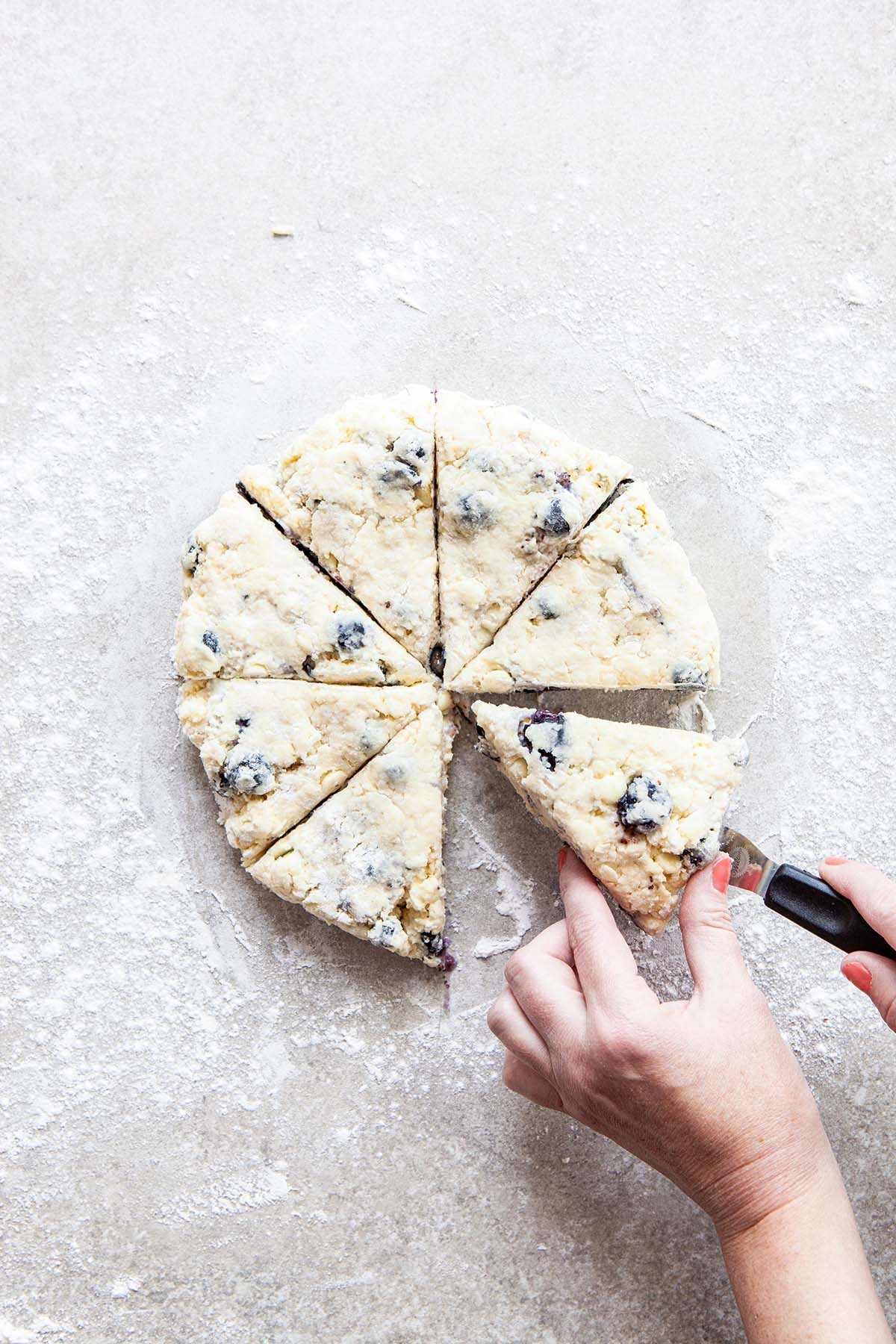 Two hands using an offset spatula to lift a wedge of scone dough from a floured stone surface.