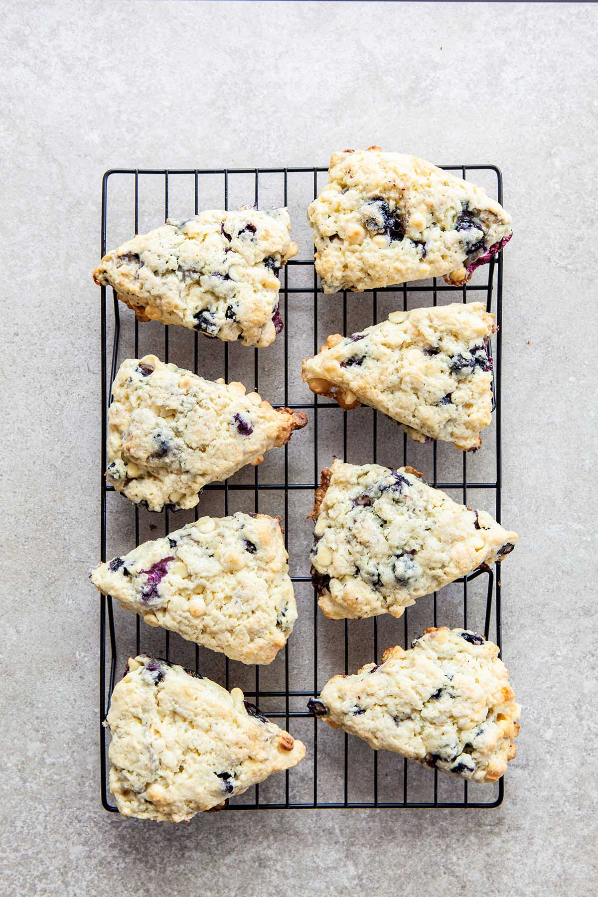 Eight blueberry white chocolate scones cooling on a rack set on a stone surface.