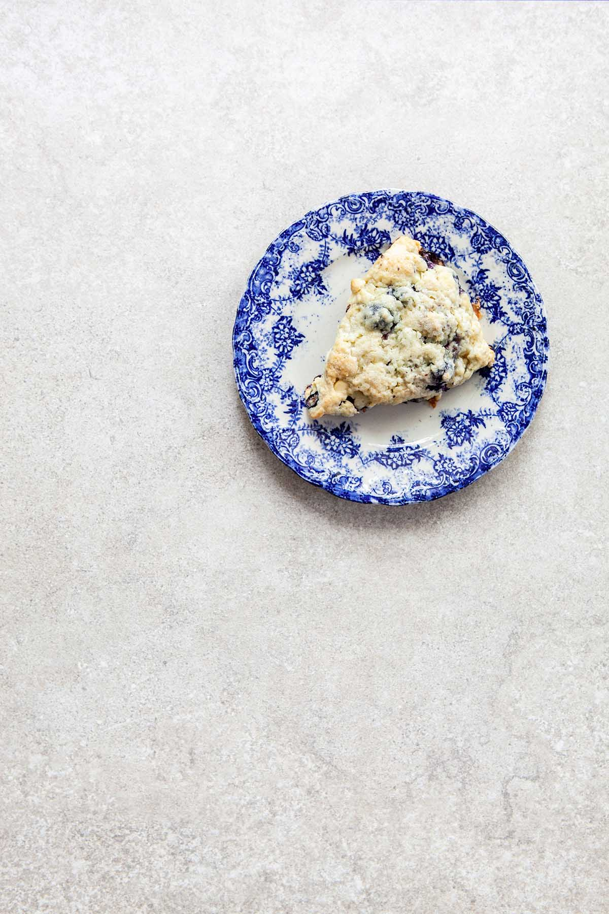 One scone on a blue and white plate on a stone surface.
