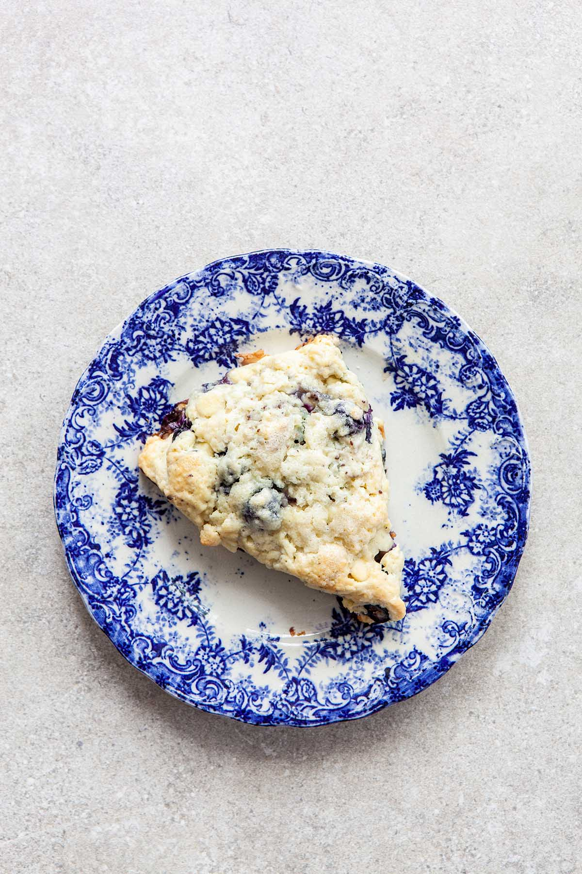 One scone on a blue and white plate laying on a stone surface.
