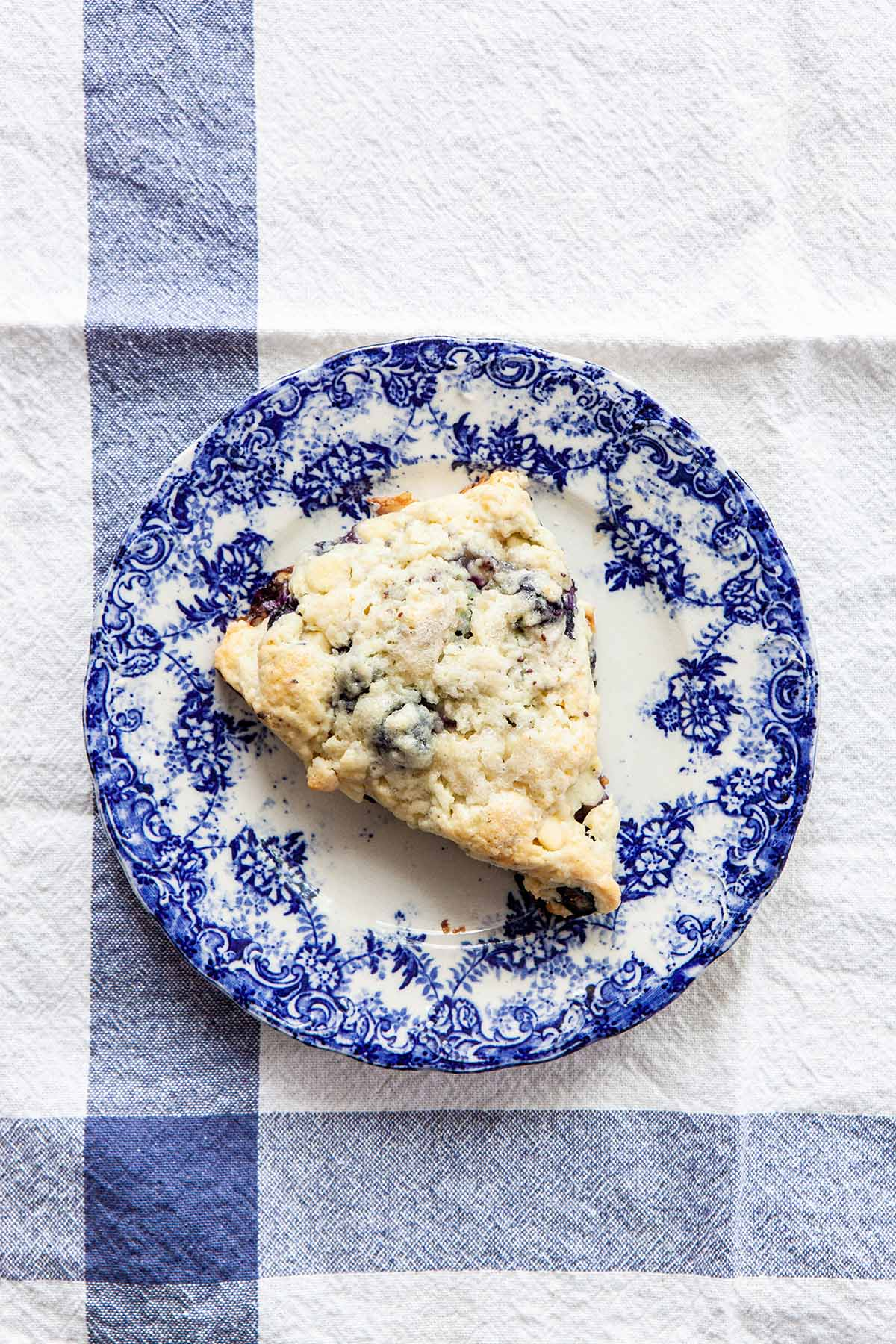 One blueberry white chocolate scone sitting on a bright blue and white plate on a white tablecloth with two blue stripes.