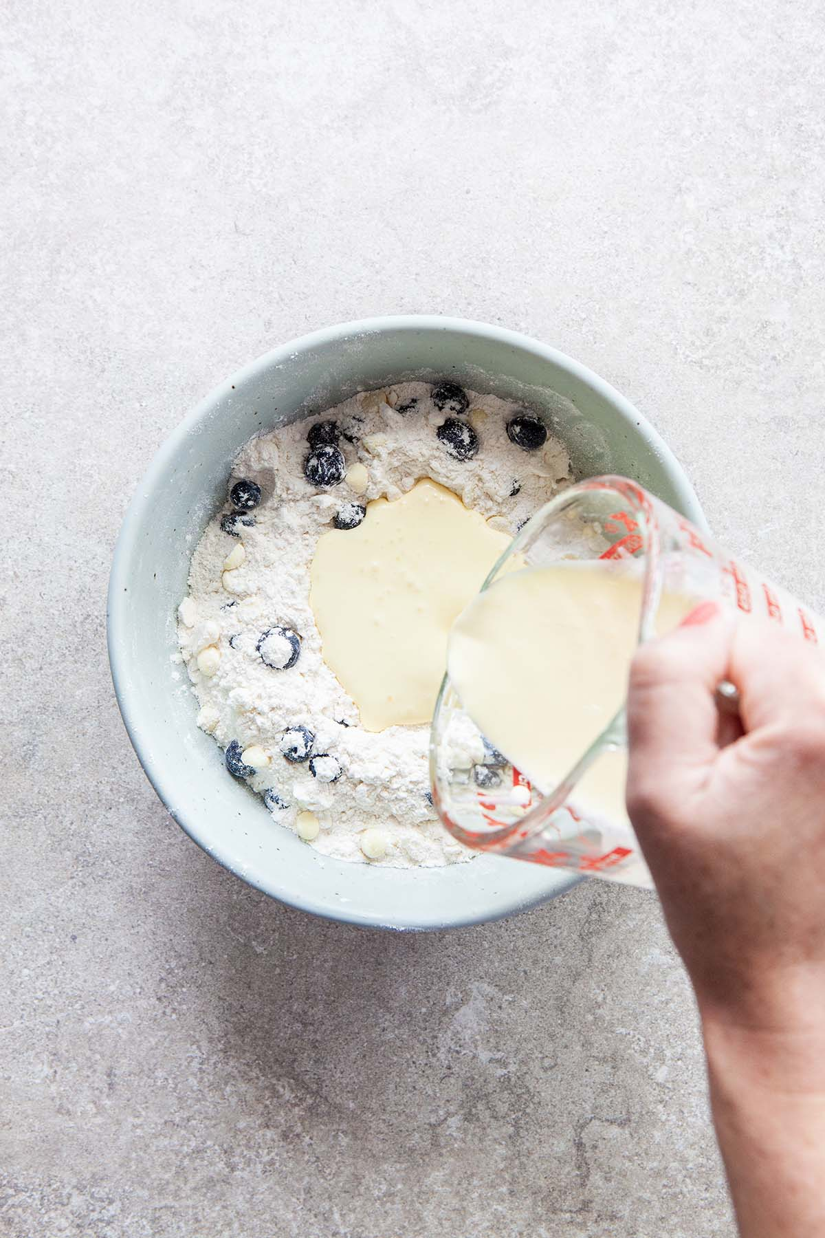A hand pouring cream into a bowl filled with flour, blueberries, and white chocolate chips.