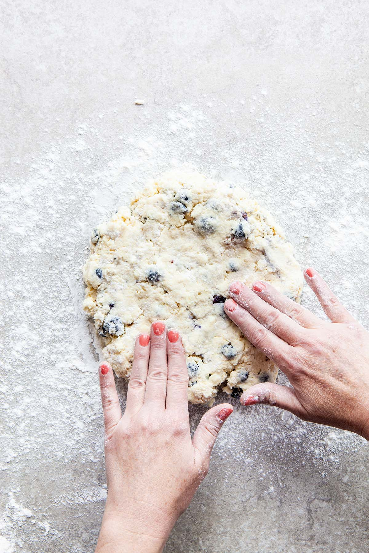 Two hands patting dough into a circle on a floured stone surface.
