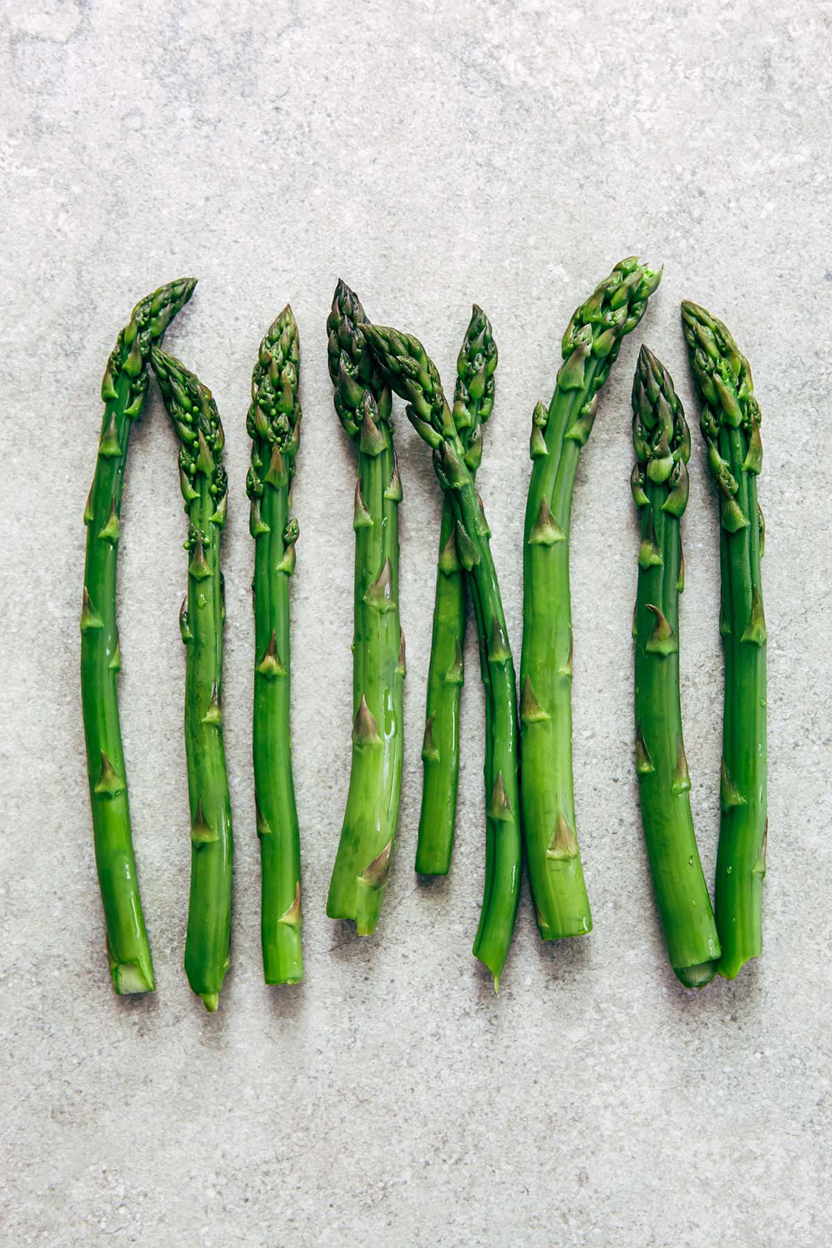 Blanched spears of asparagus laying on a stone surface.