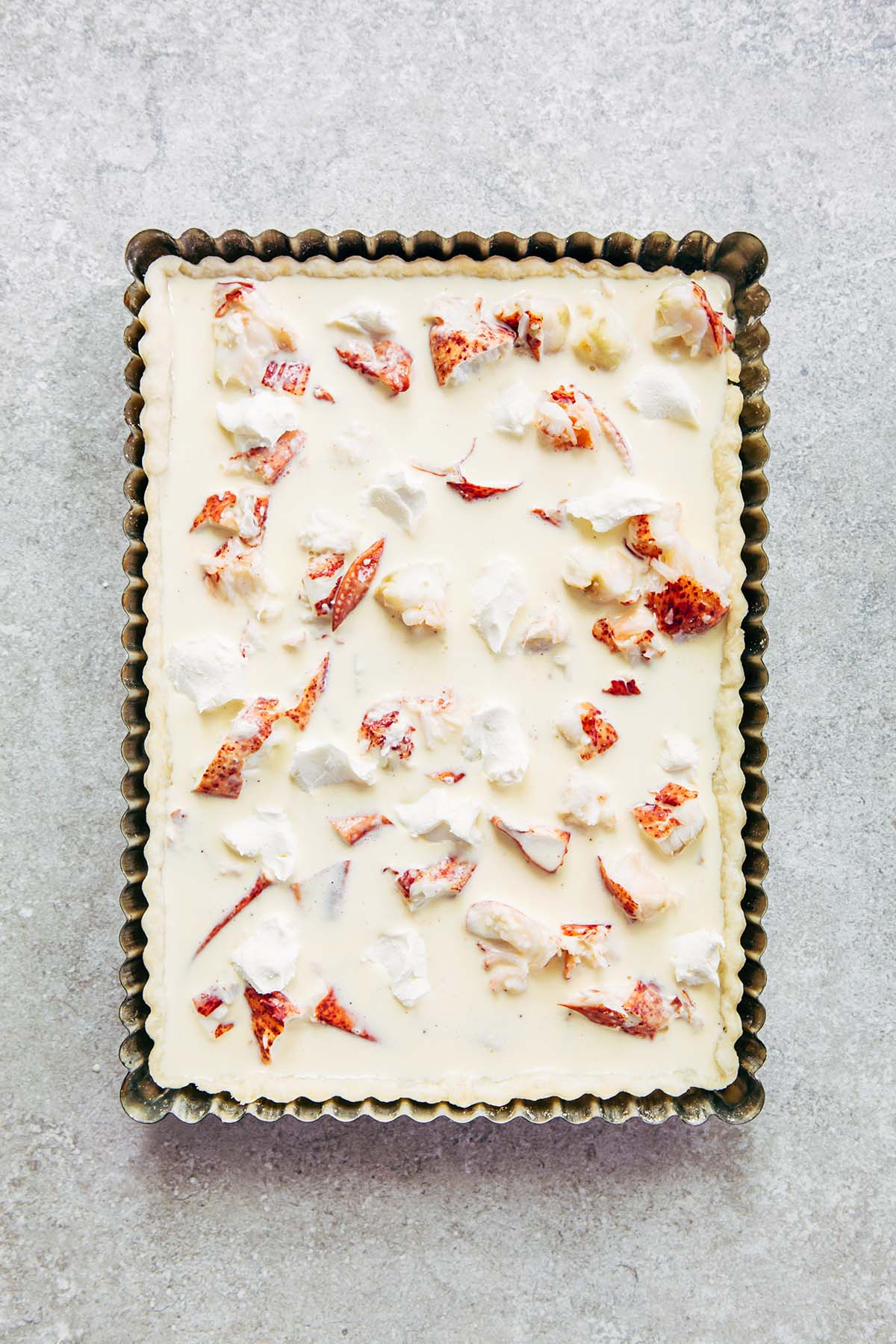 An unbaked rectangular quiche in a metal tart tin with pieces of cooked lobster and cream cheese throughout.