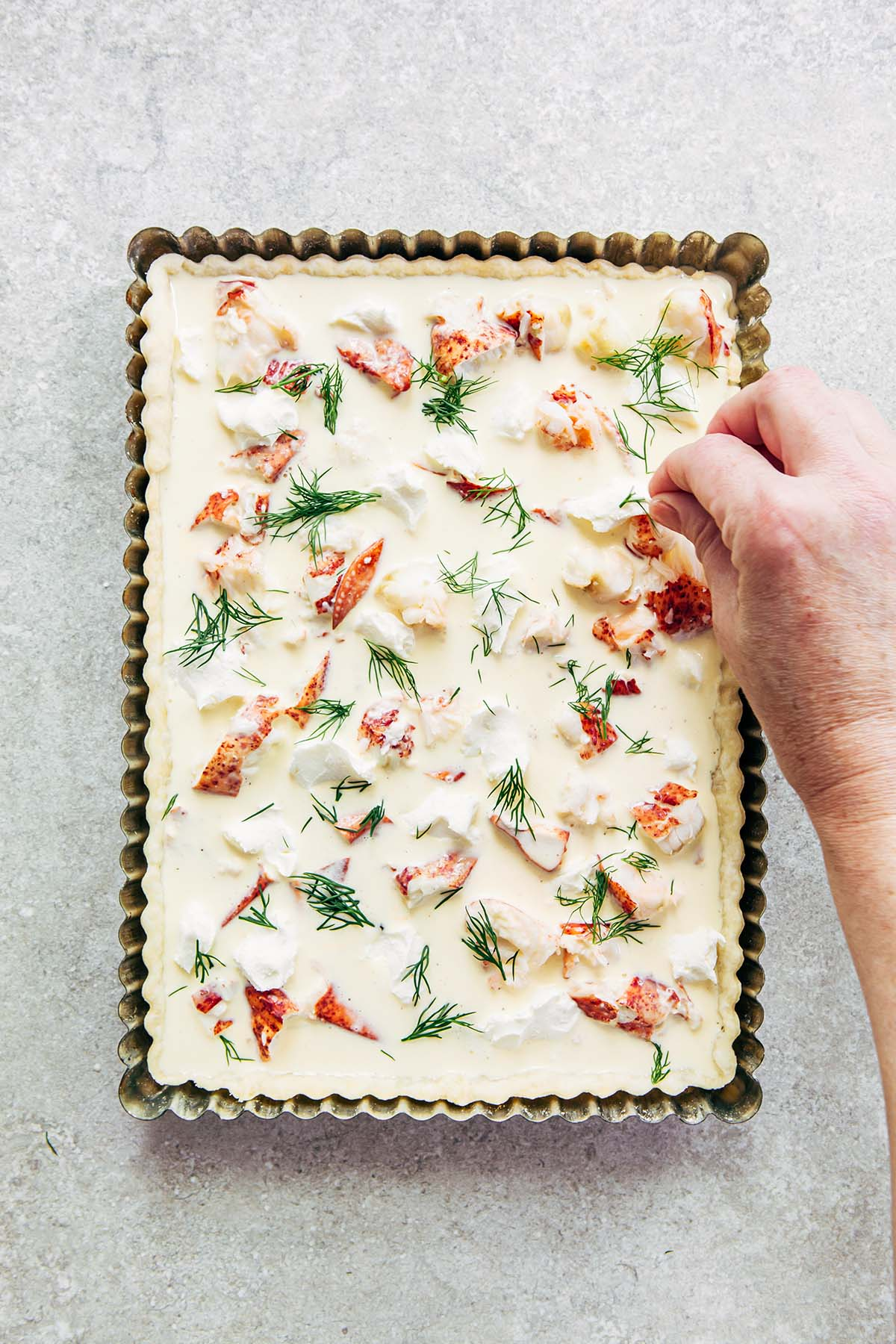 A woman's hand sprinkling pieces of fresh dill over an unbaked quiche in a rectangle metal tart tin on a stone surface.