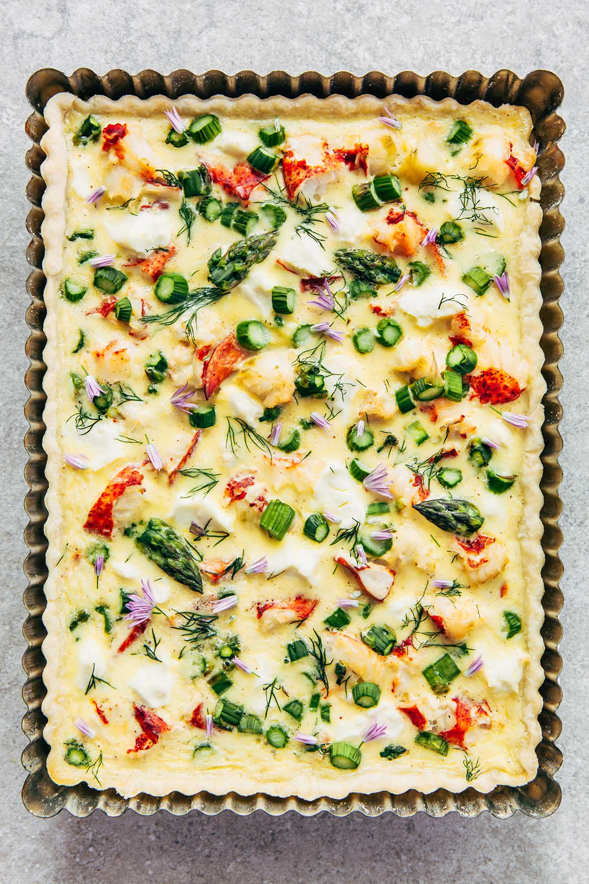 Overhead close up of a lobster quiche with cream cheese and asparagus in a rectangular metal tart tin on a stone surface.