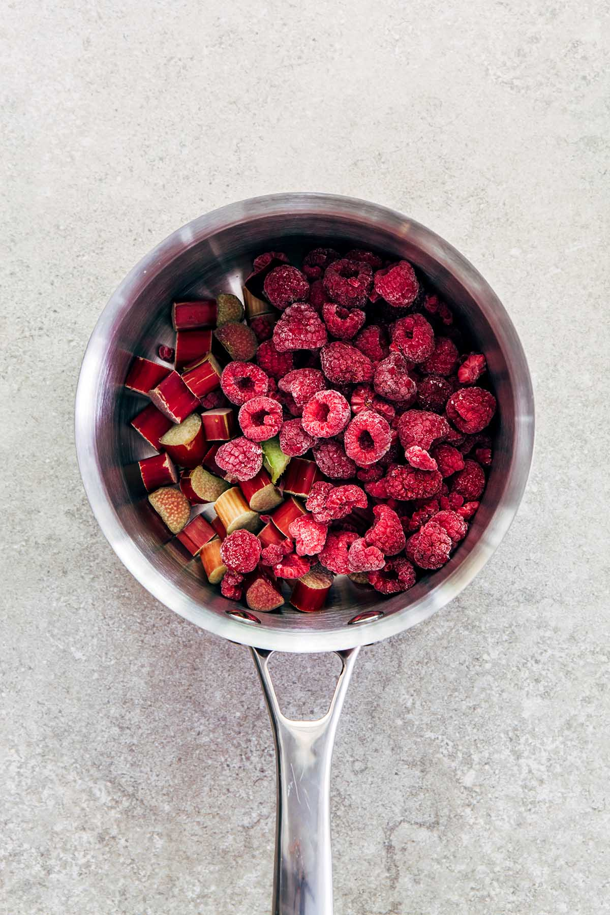 Rhubarb and frozen raspberries in a small silver pot shot from overhead.