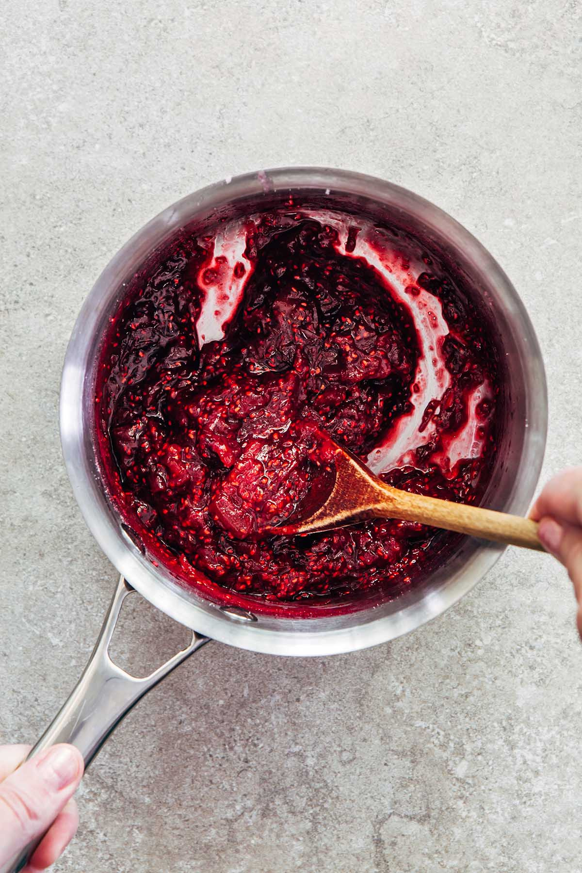 Cooked jam in a pot on a stone surface being stirred with a wooden spoon.