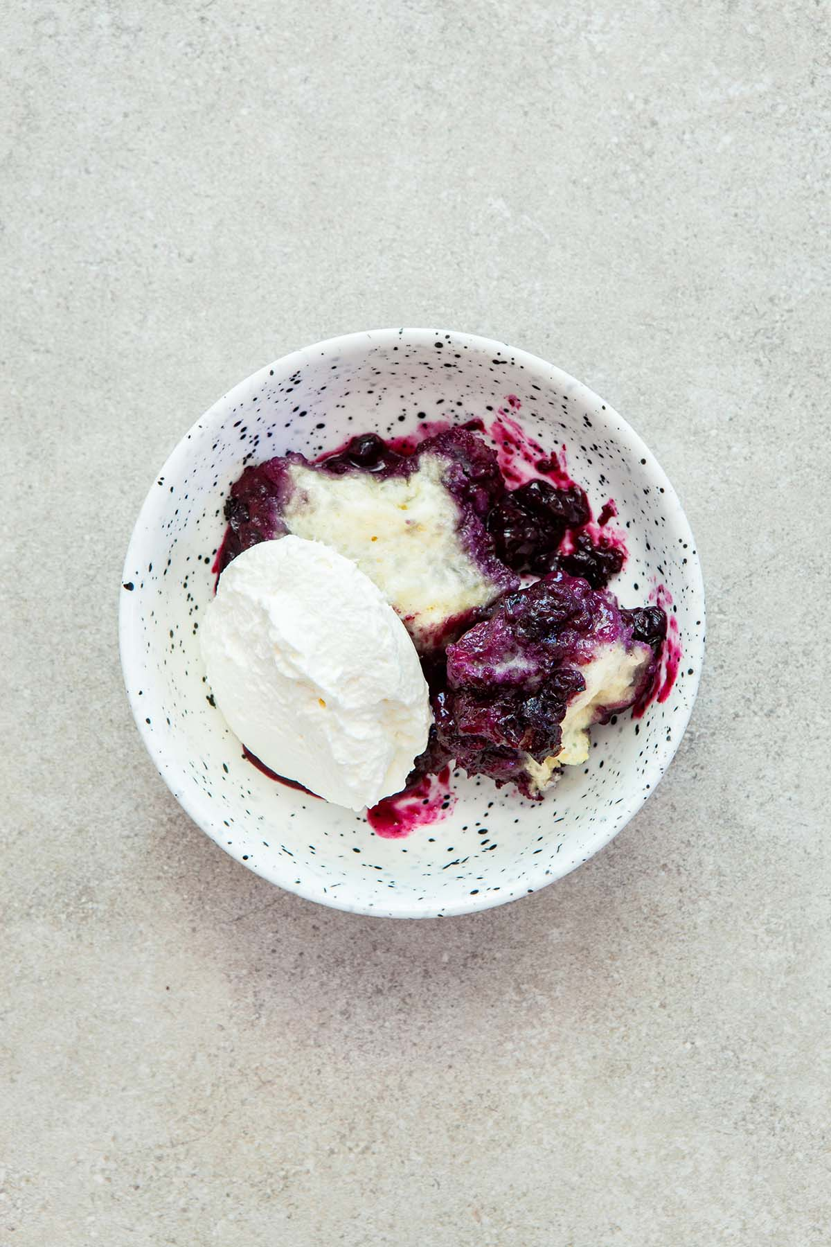 A bowl of blueberry grunt topped with whipped cream in a small white speckled bowl.