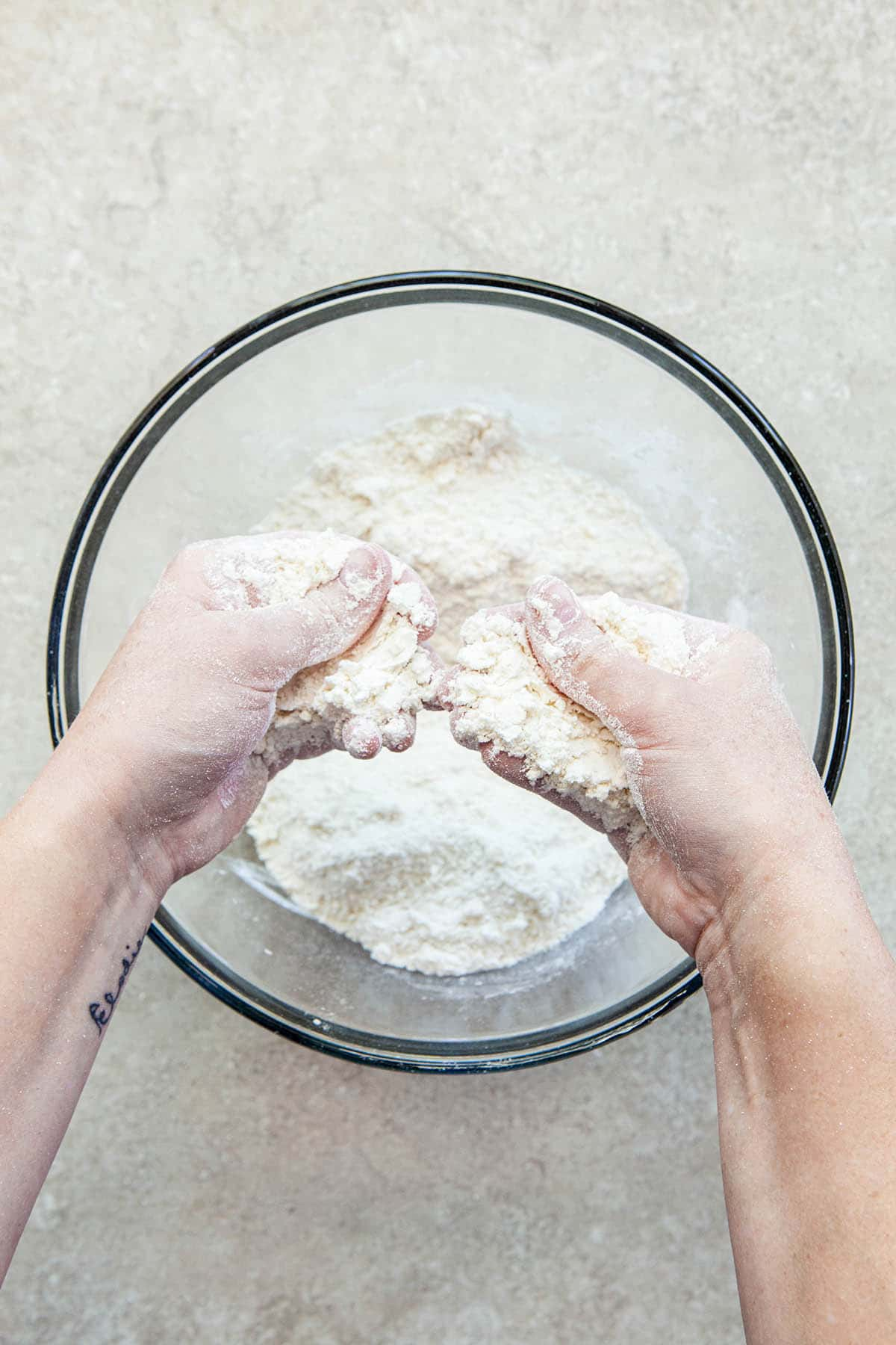 Two hands rubbing butter into flour in a glass bowl.
