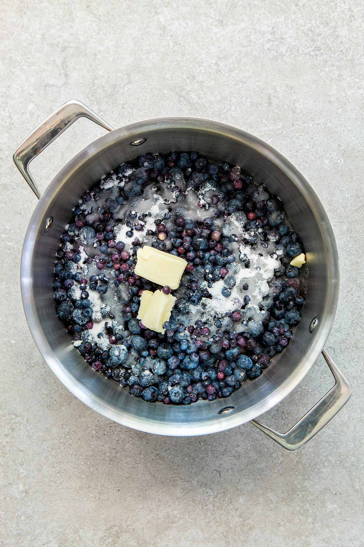 A silver pot with handles with wild blueberries, sugar, water, and chunks of butter inside.