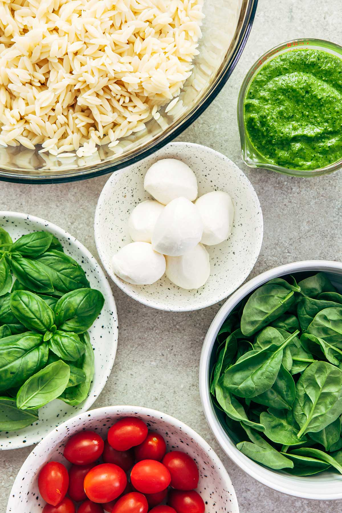 Overhead shot of a bowl of cooked orzo, a cup of pesto, and bowls of baby spinach, bocconcini, cherry tomatoes, and fresh basil leaves.